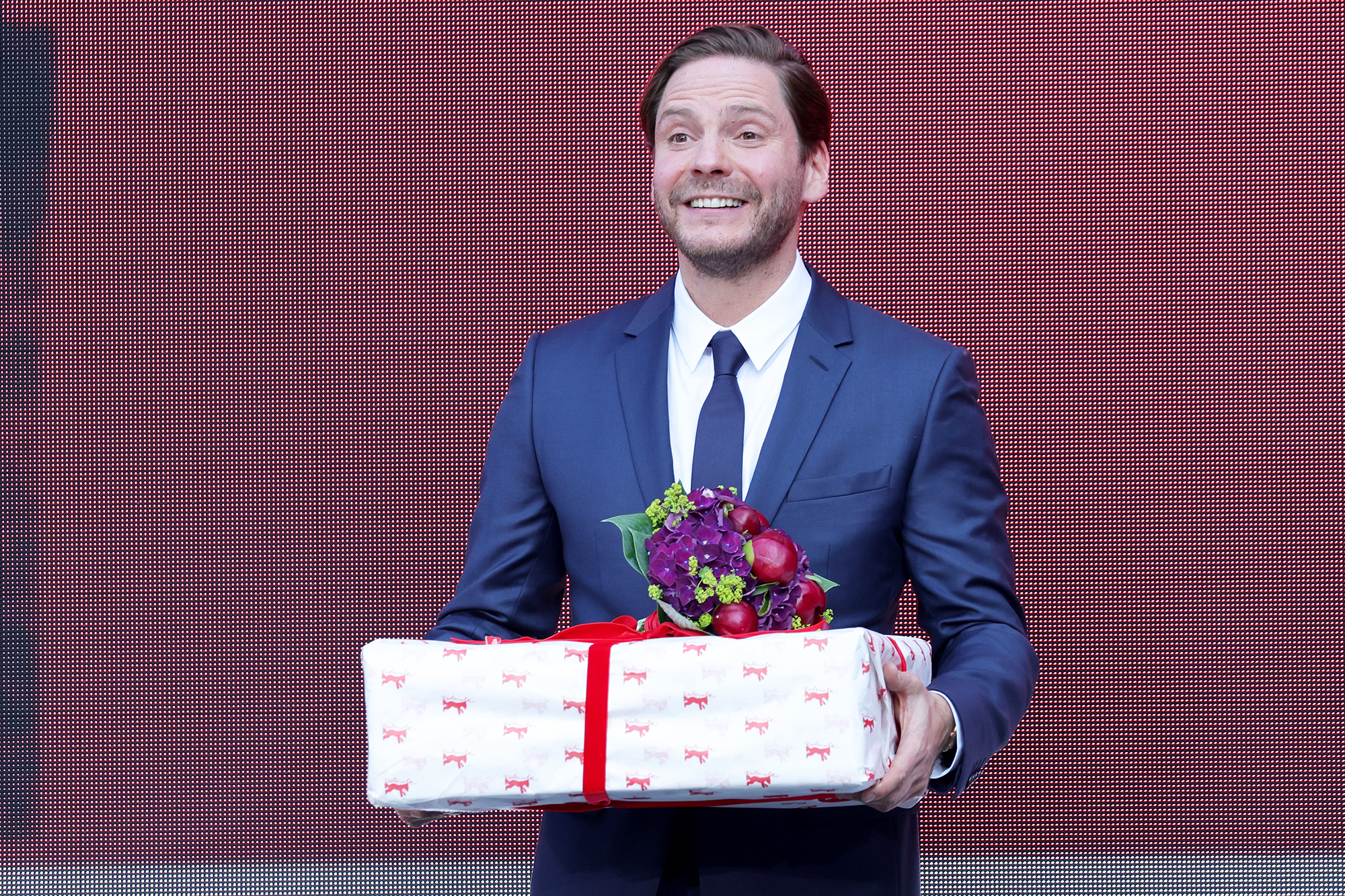 """Daniel Bruehl receives a birthday present at the """"Nebenan"""" (Next Door) premiere during the 71st Berlinale International Film Festival Summer Special at Freiluftkino Museumsinsel on June 16, 2021 in Berlin, Germany"""
