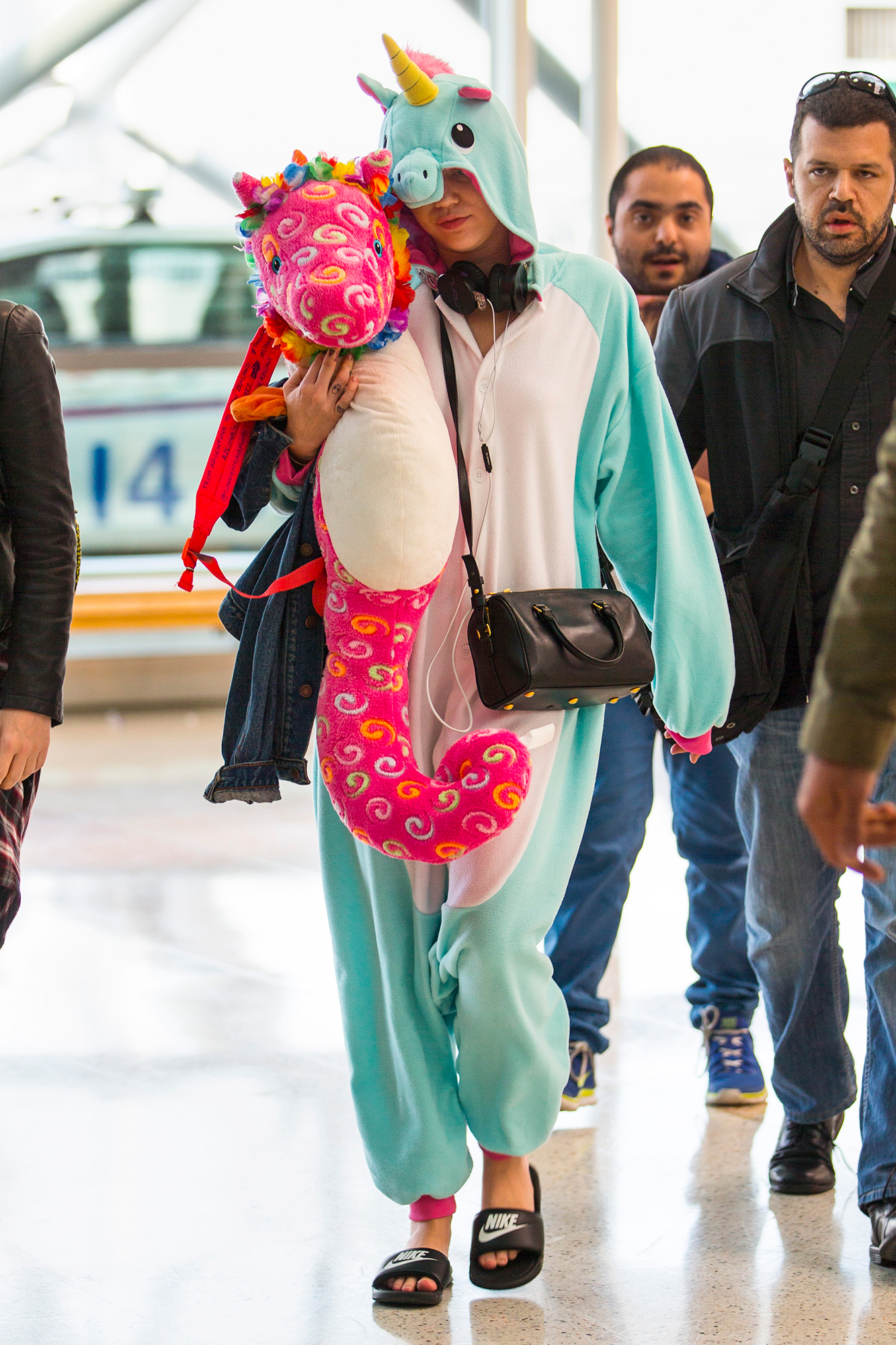 Miley Cyrus wears a unicorn onesie and holds a toy unicorn through Sydney Airport