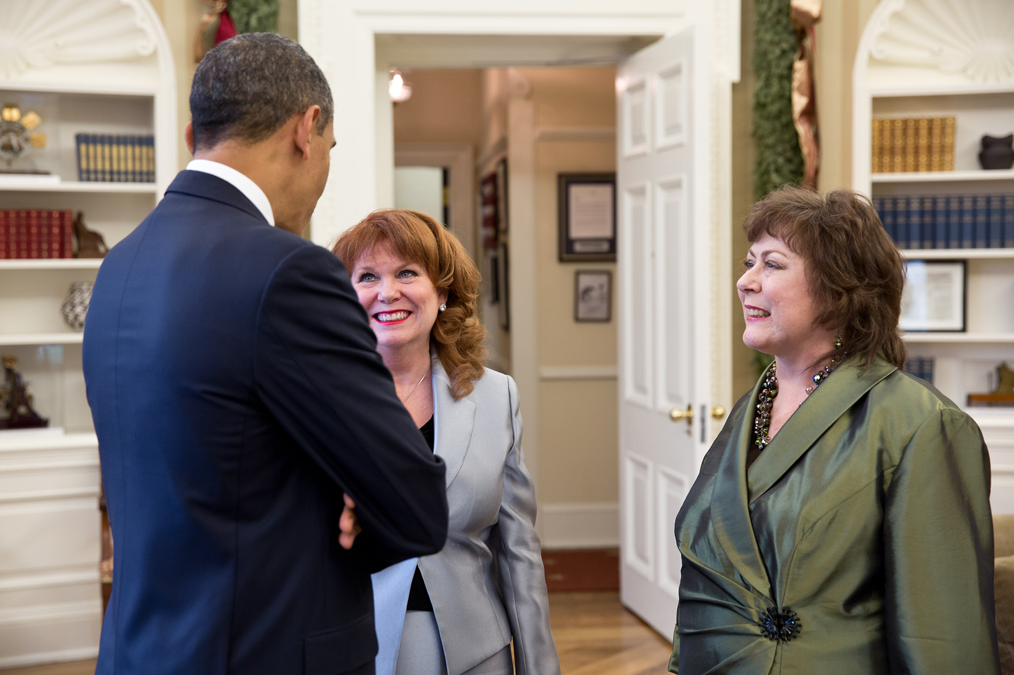 President Barack Obama talks with Natoma Canfield, right, and her sister, Connie Anderson, in the Oval Office, Dec. 12, 2012. The letter Canfield sent the President in 2010 hangs on the wall in the background.