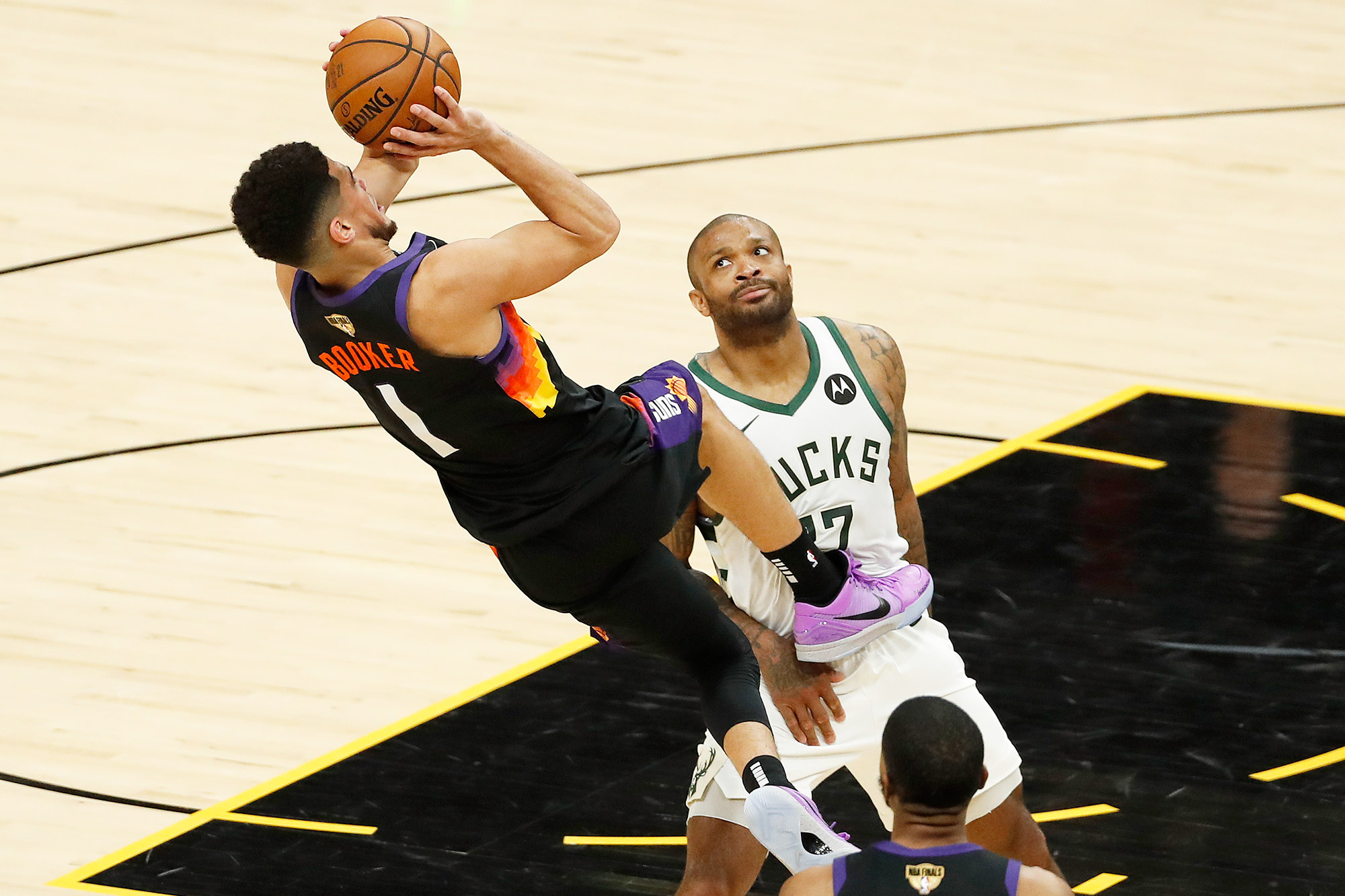 Devin Booker #1 of the Phoenix Suns is fouled by P.J. Tucker #17 of the Milwaukee Bucks during the first half in Game One of the NBA Finals at Phoenix Suns Arena on July 06, 2021 in Phoenix, Arizona