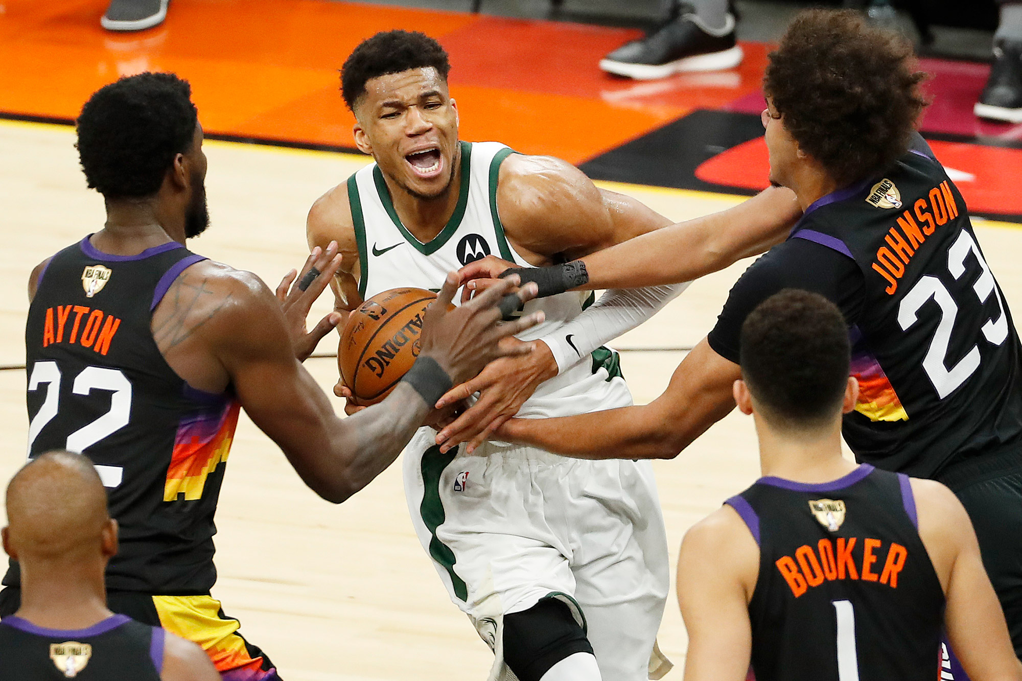 Giannis Antetokounmpo #34 of the Milwaukee Bucks is pressured by Deandre Ayton #22 and Cameron Johnson #23 of the Phoenix Suns during the second half in Game One of the NBA Finals at Phoenix Suns Arena on July 06, 2021 in Phoenix, Arizona