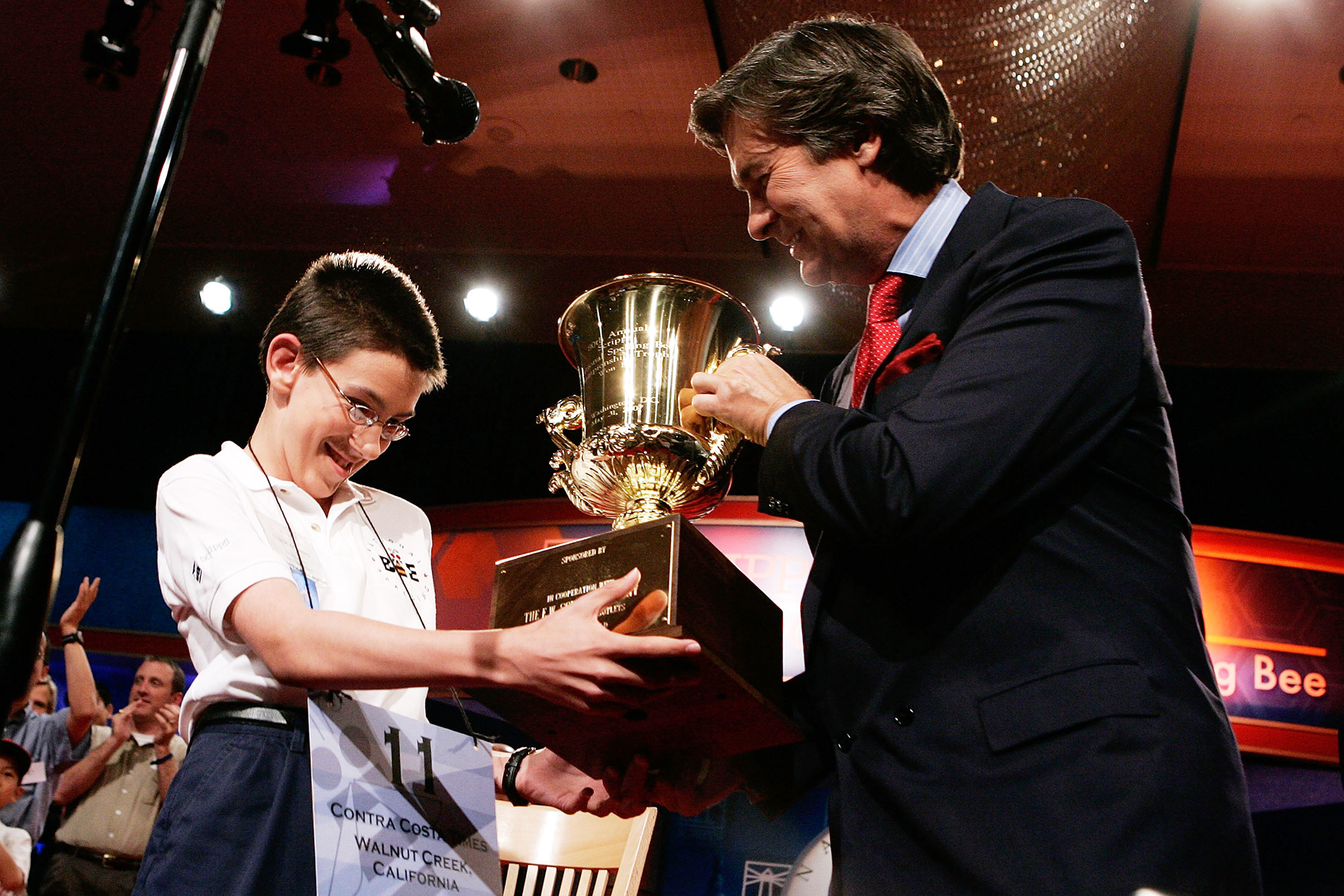 Speller Evan O'Dorney (L) of Danville, California, receives a trophy from Kenneth Lowe, President and CEO of the E.W. Scripps Company, after O'Dorney won the finals of 2007 Scripps National Spelling Bee May 31, 2007 in Washington, DC