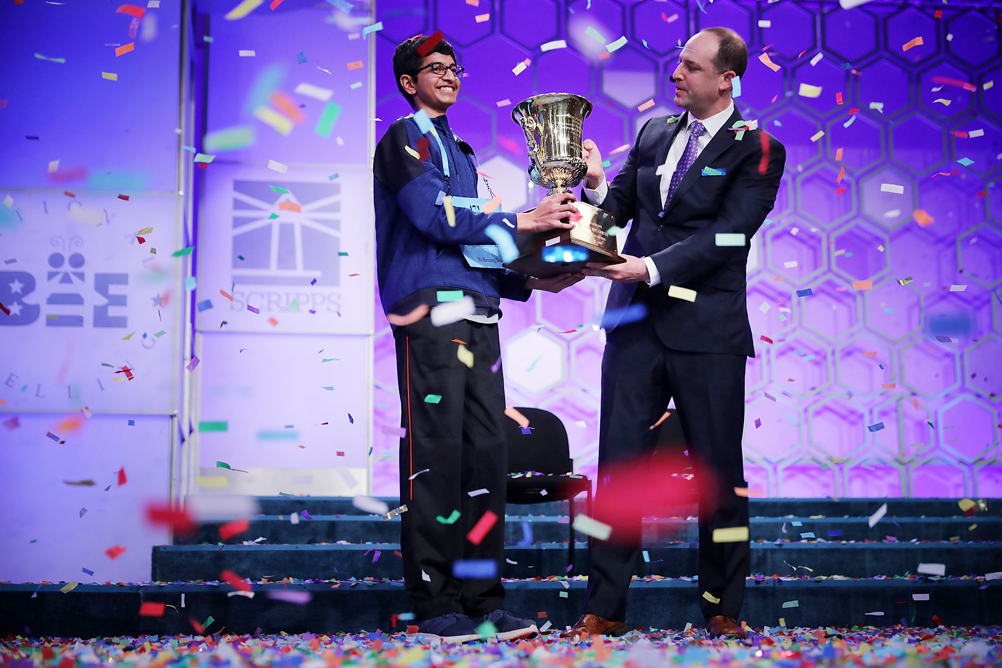 Karthik Nemmani (L) poses with the championship trophy and E.W. Scripps Company CEO Adam Symson after Nemmani correctly spelled the word 'koinonia' to win the 91st Scripps National Spelling Bee at the Gaylord National Resort and Convention Center May 31, 2018 in National Harbor, Maryland