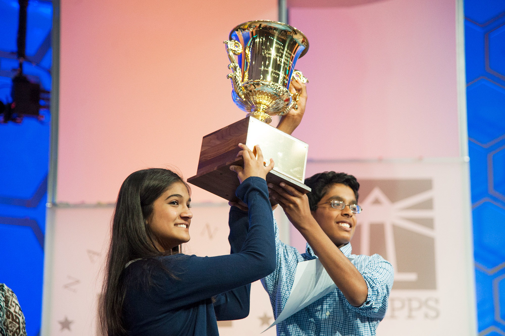 Spelling Bee contestants Vanya Shivashankar, 13, of Olathe, KS (90) and Gokul Venkatachalam, 14, of Chesterfield, MO (140) co-champions hoist the trophy during the final round of the Scripps National Spelling Bee May 28, 2015 at National Harbor, MD