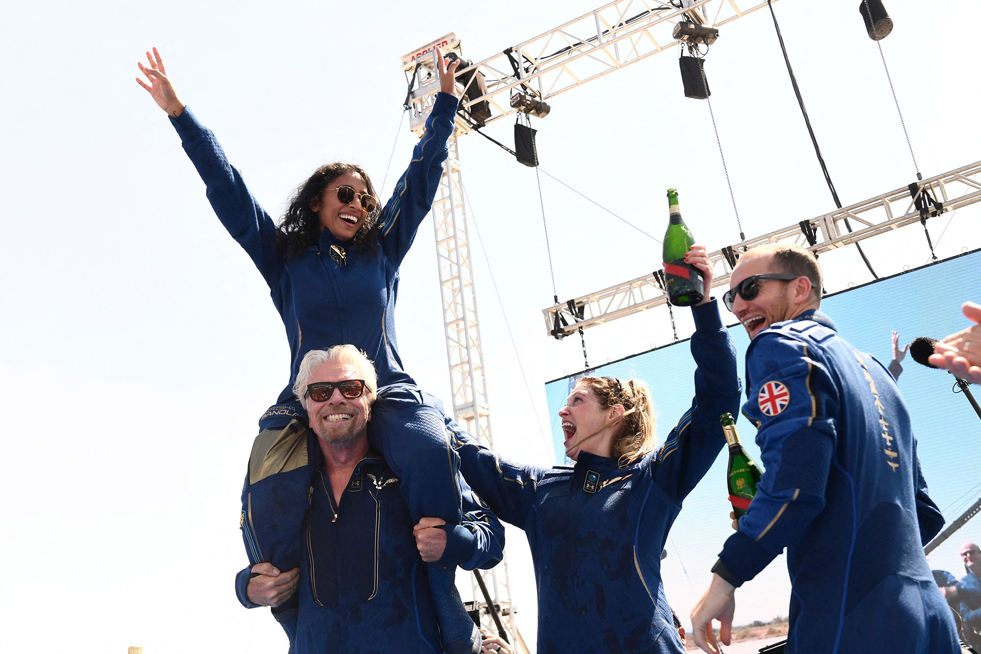 """Virgin Galactic founder Sir Richard Branson(L), with Sirisha Bandla on his shoulders, cheers with crew members after flying into space aboard a Virgin Galactic vessel, a voyage he described as the """"experience of a lifetime"""" -- and one he hopes will usher in an era of lucrative space tourism at Spaceport America, near Truth and Consequences, New Mexico on July 11, 2021. -"""