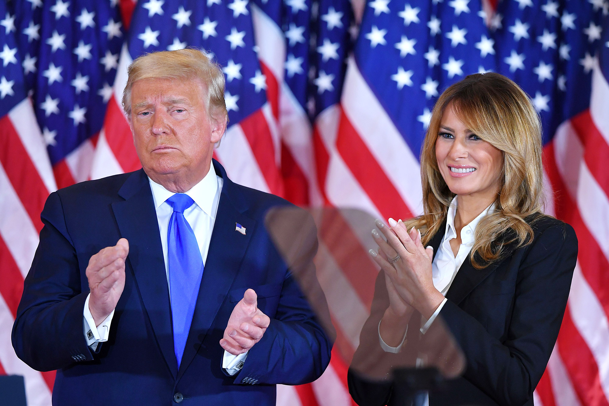President Donald Trump claps alongside US First Lady Melania Trump after speaking during election night in the East Room of the White House in Washington, DC, early on November 4, 2020