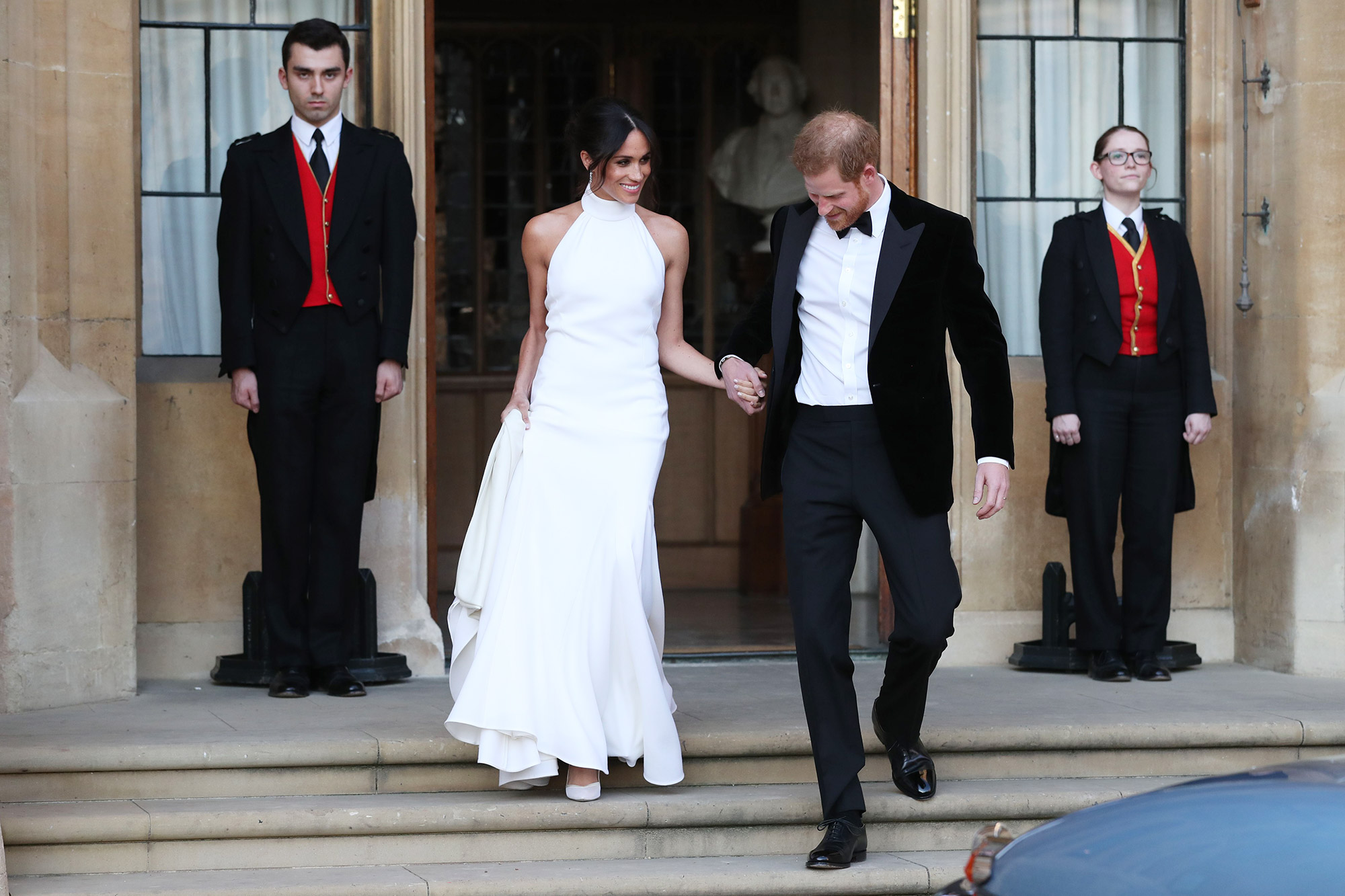 The newly married Britain's Prince Harry, Duke of Sussex, (R) and Meghan Markle, Duchess of Sussex, (L) leave Windsor Castle in Windsor on May 19, 2018 after their wedding to attend an evening reception at Frogmore House.