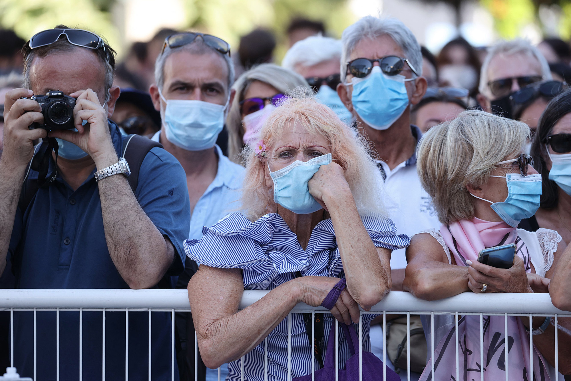 """Onlookers wearing masks for protection against the COVID-19 pandameic watch guests arriving for the screening of the film """"Benedetta"""" at the 74th edition of the Cannes Film Festival in Cannes"""