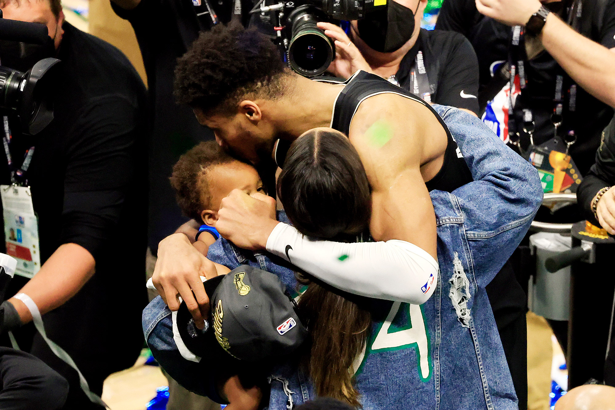 Giannis Antetokounmpo #34 of the Milwaukee Bucks celebrates with his family after defeating the Phoenix Suns