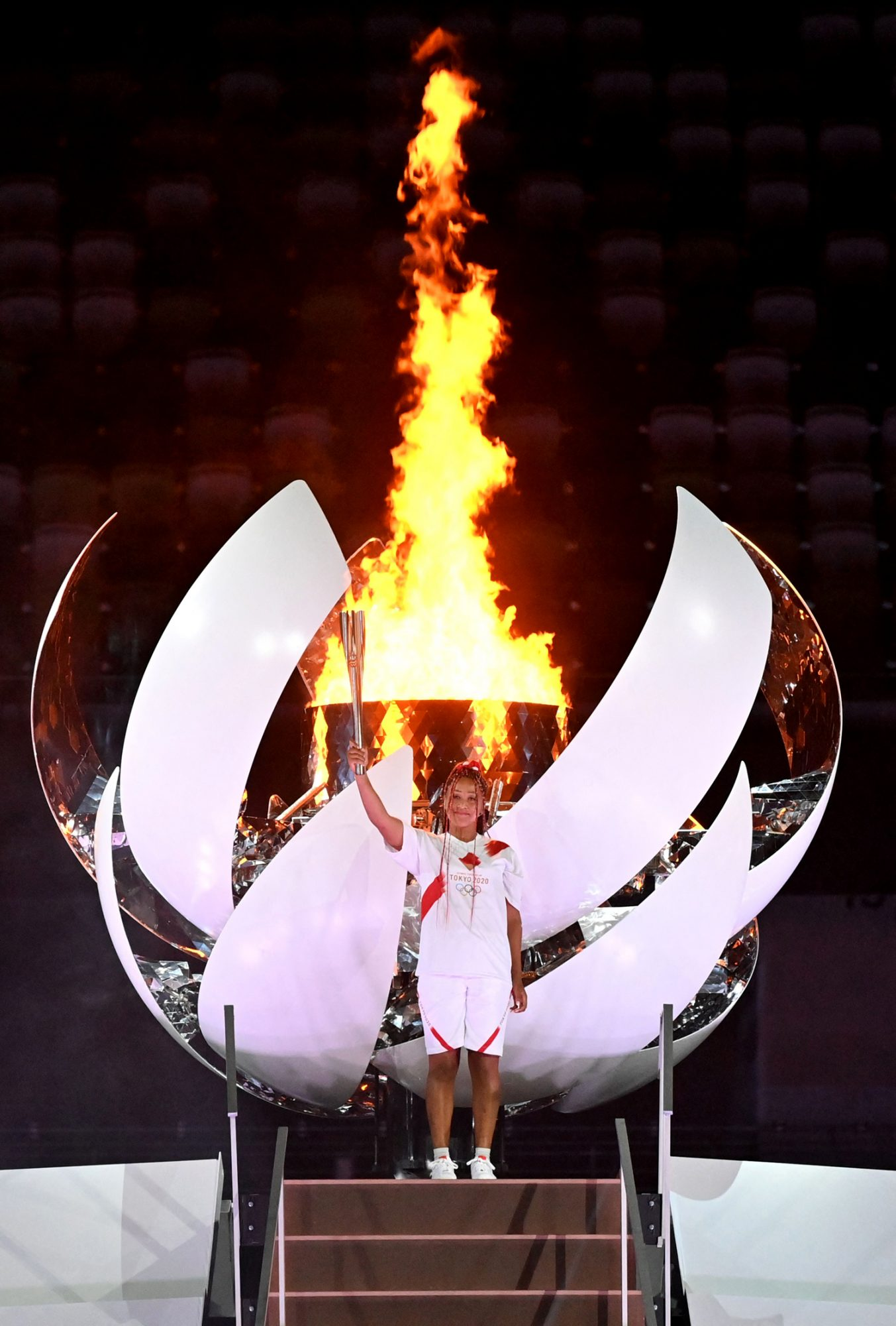Naomi Osaka poses after lighting the Olympic Cauldron with the Olympic flame