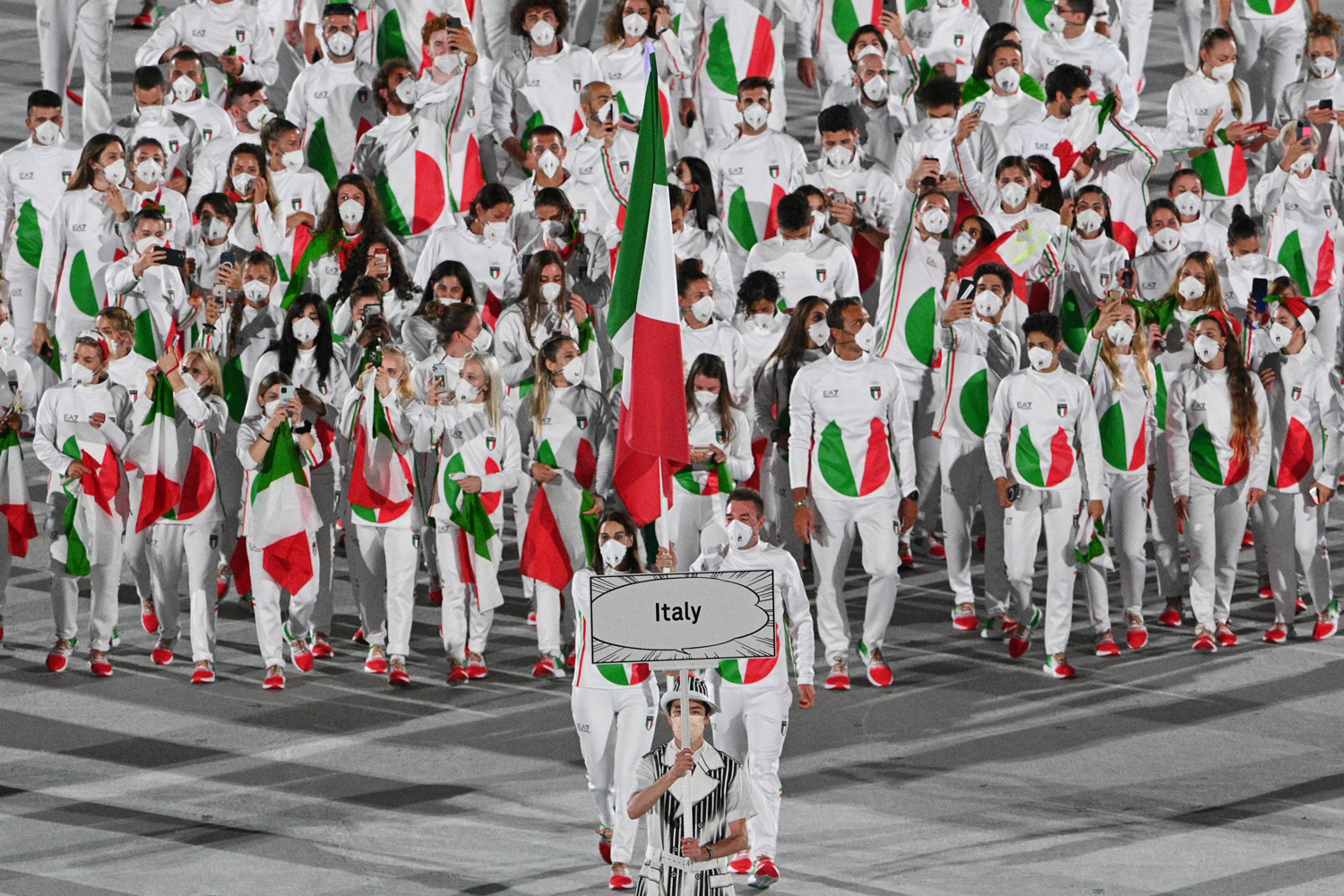 Italy's flag bearer Jessica Rossi (L) and Italy's flag bearer Elia Viviani lead the delegation during the opening ceremony of the Tokyo 2020 Olympic Games