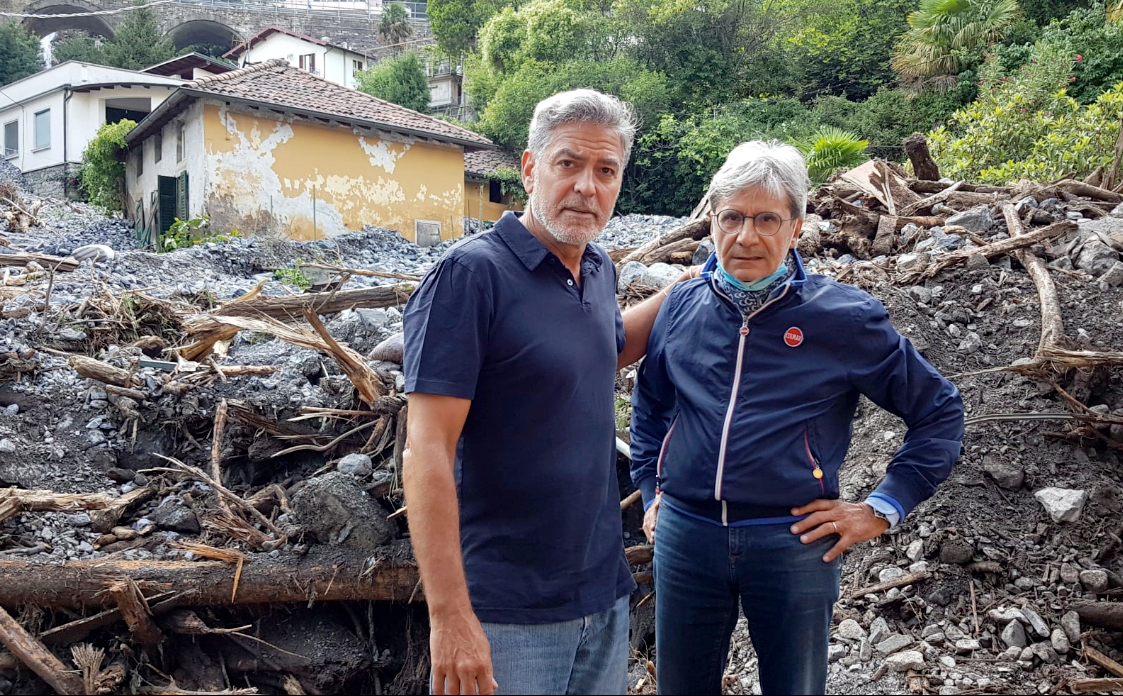 Mayor of Laglio Roberto Pozzi with George Clooney in the midst of rubble caused by bad weather in Laglio on July 28, 2021.