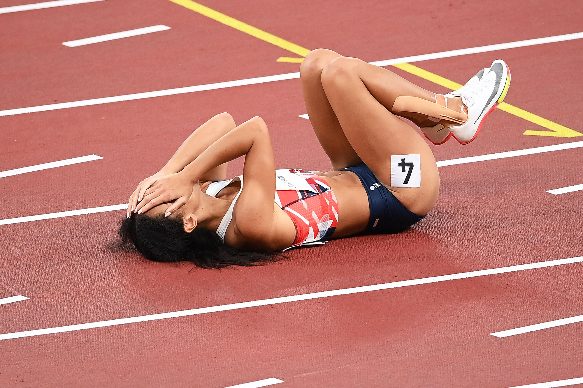 Katarina Johnson-Thompson of Team Great Britain reacts as she lies injured after the Women's Heptathlon 200m heats on day twelve of the Tokyo 2020 Olympic Games at Olympic Stadium on August 04, 2021 in Tokyo, Japan