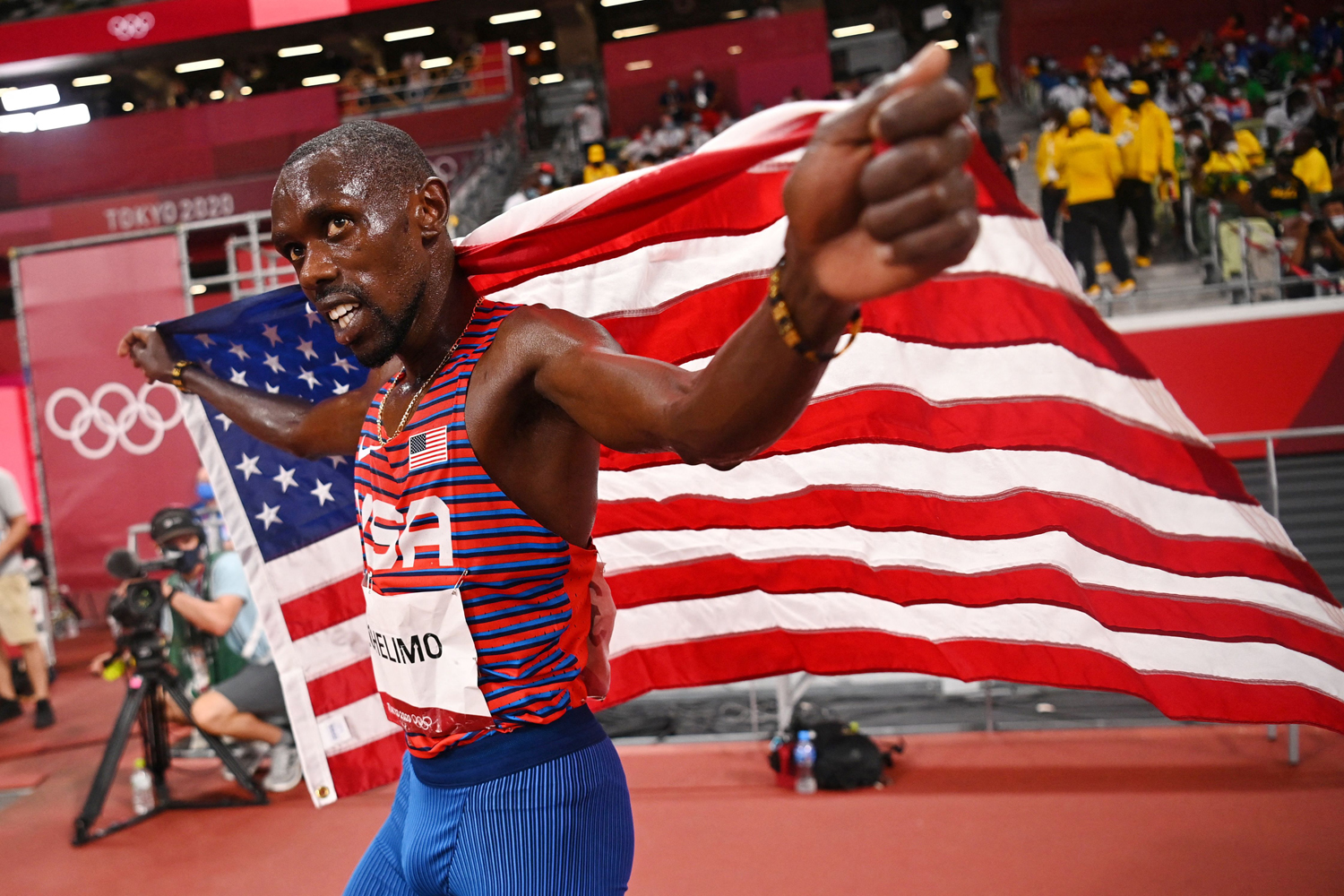 USA's Paul Chelimo celebrates with the national flag after winning the bronze medal in the men's 5000m final