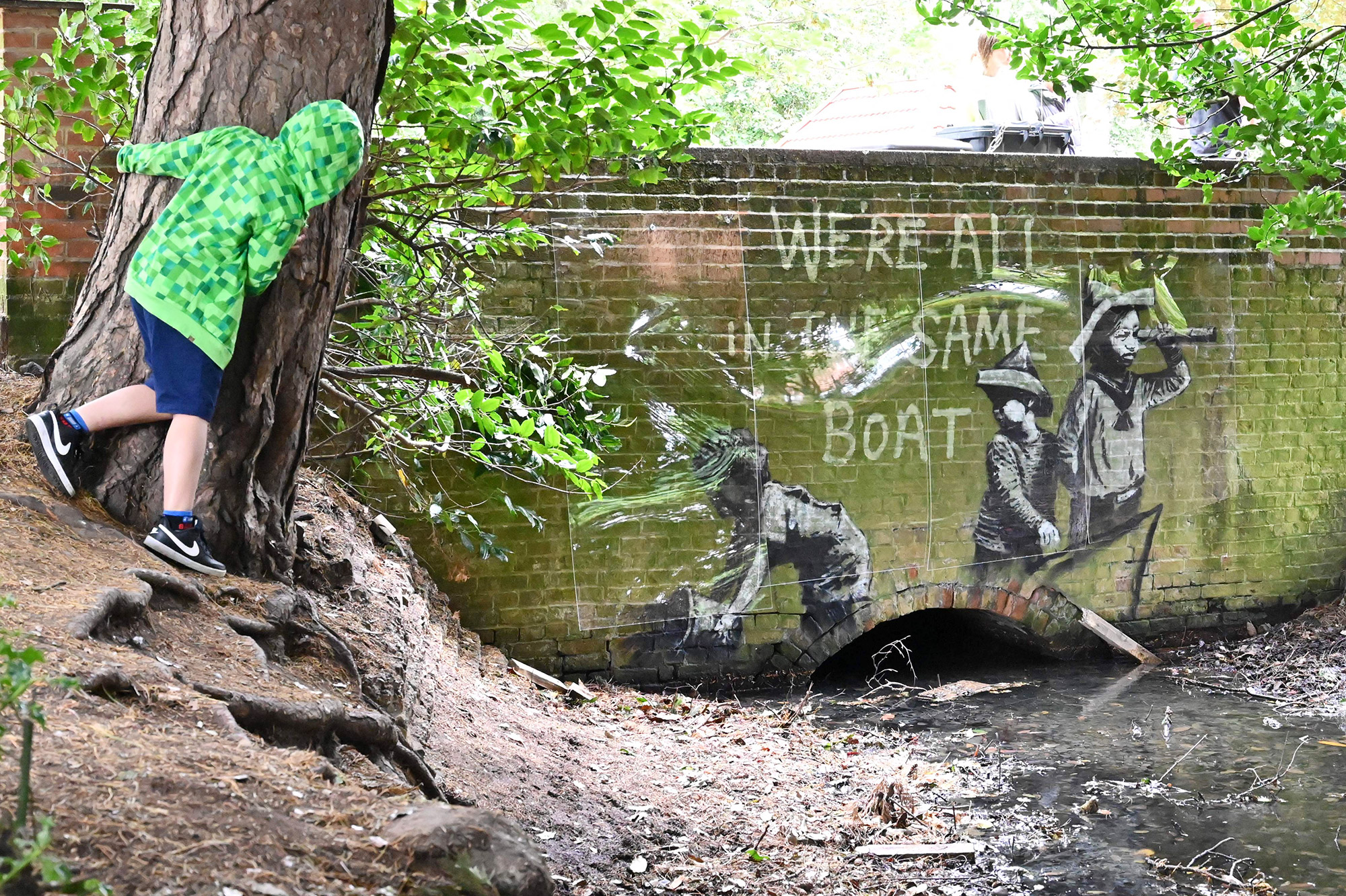 A stensil of children playing at being sailors is the subject of a graffiti artwork bearing the hallmarks of street artist Banksy on the wall of a bridge in Everitt Park in Lowestoft on the East coast of England on August 8, 2021.