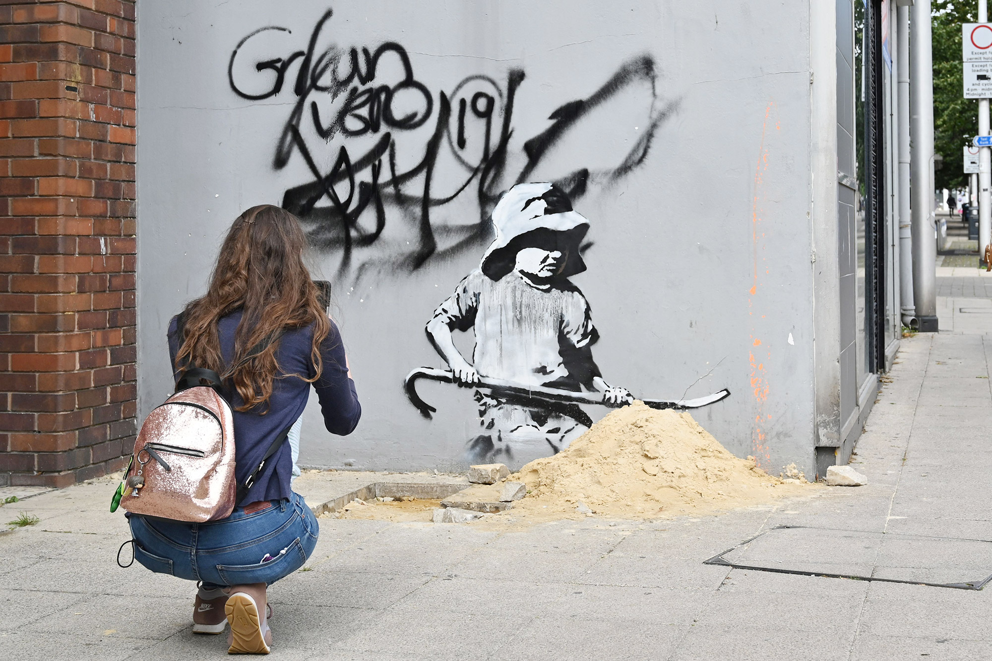 A woman takes a photograph of a stensil of a child digging in the sand, the subject of a graffiti artwork bearing the hallmarks of street artist Banksy on a wall in Lowestoft on the East coast of England on August 8, 2021.