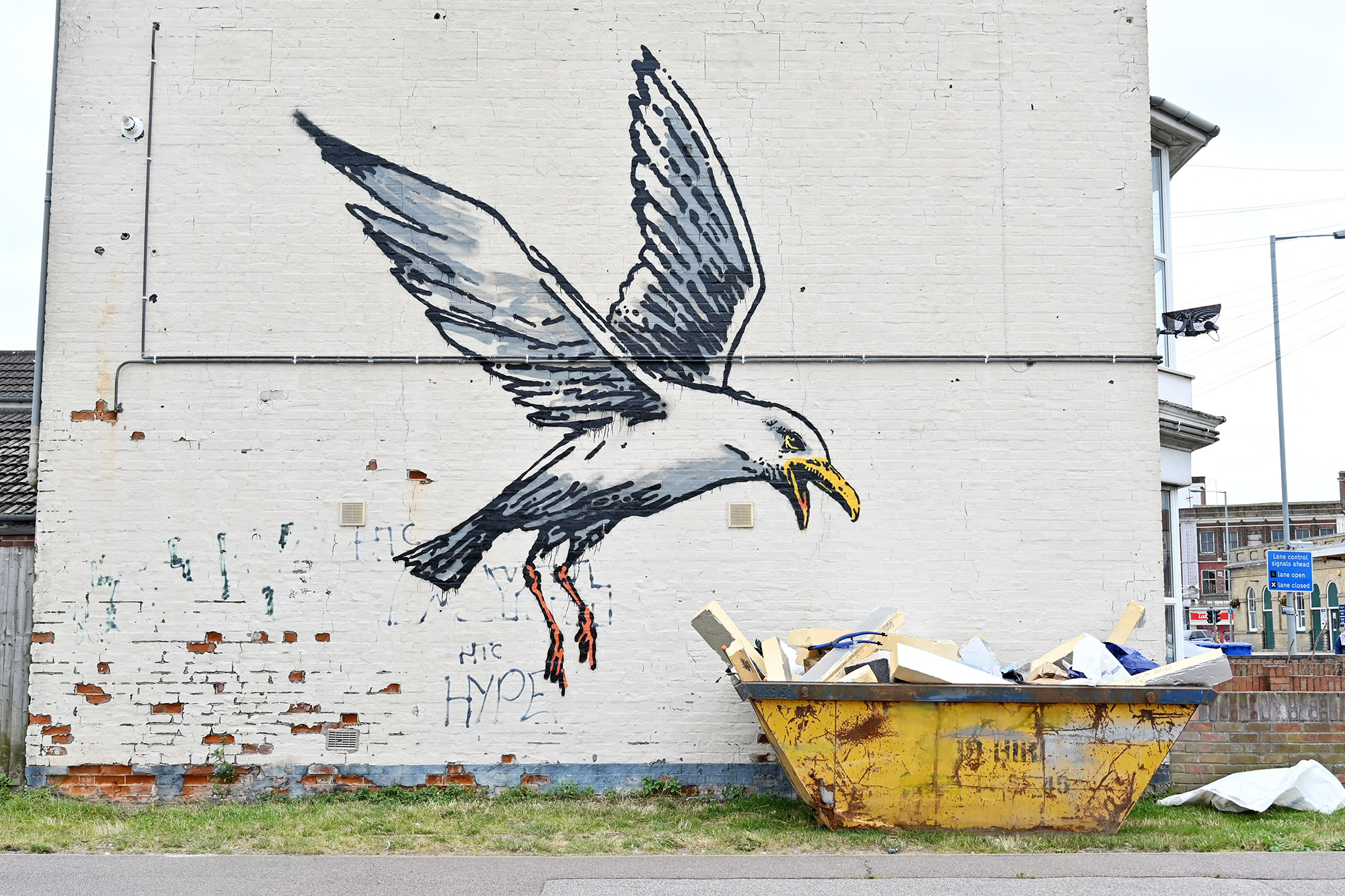 A stensil of a gull about to swoop down onto a carton of chips is the subject of a graffiti artwork bearing the hallmarks of street artist Banksy on a wall in Lowestoft on the East coast of England on August 8, 2021.