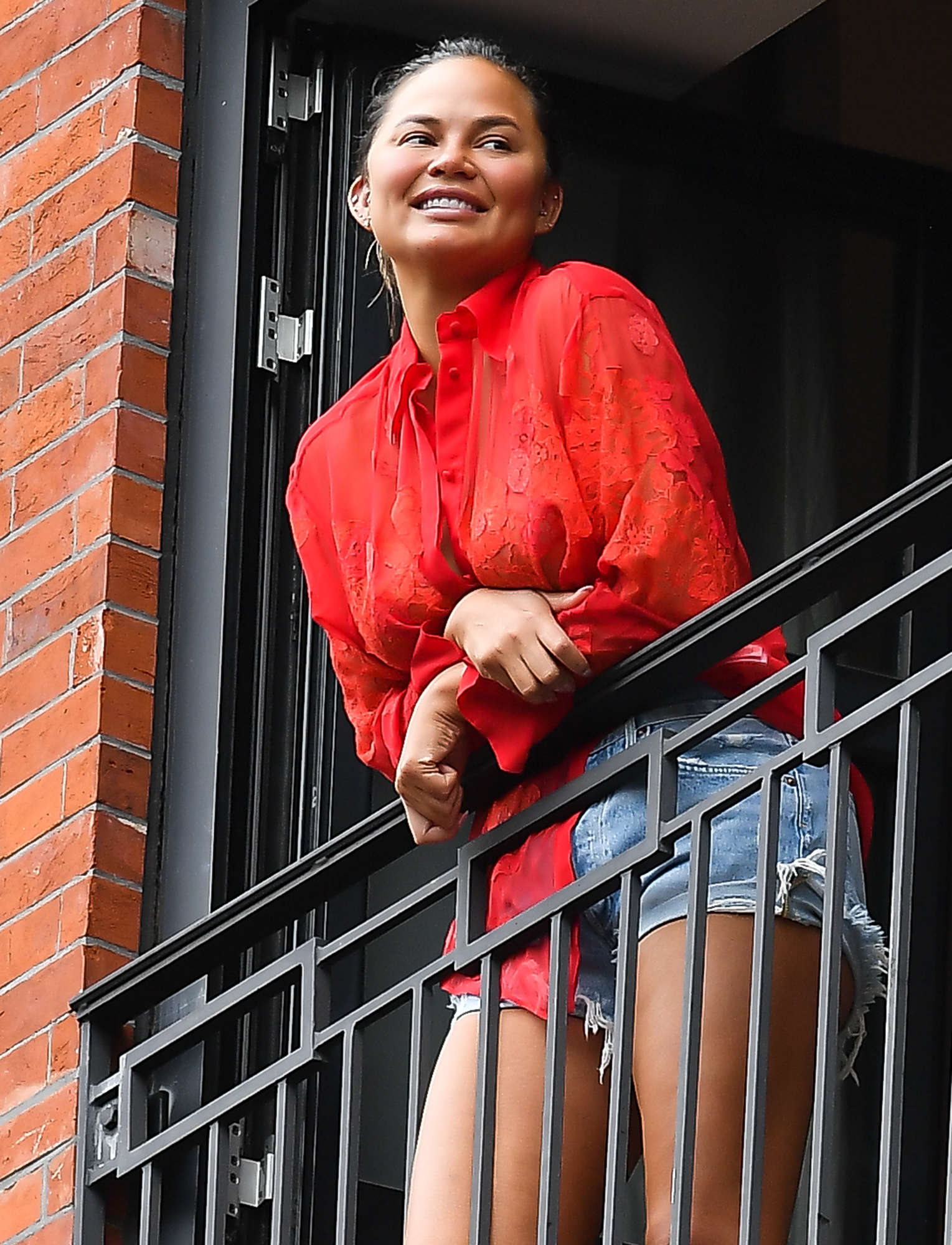 Chrissy Teigen Wears A Red Top And Jean Shorts In Soho, New York City