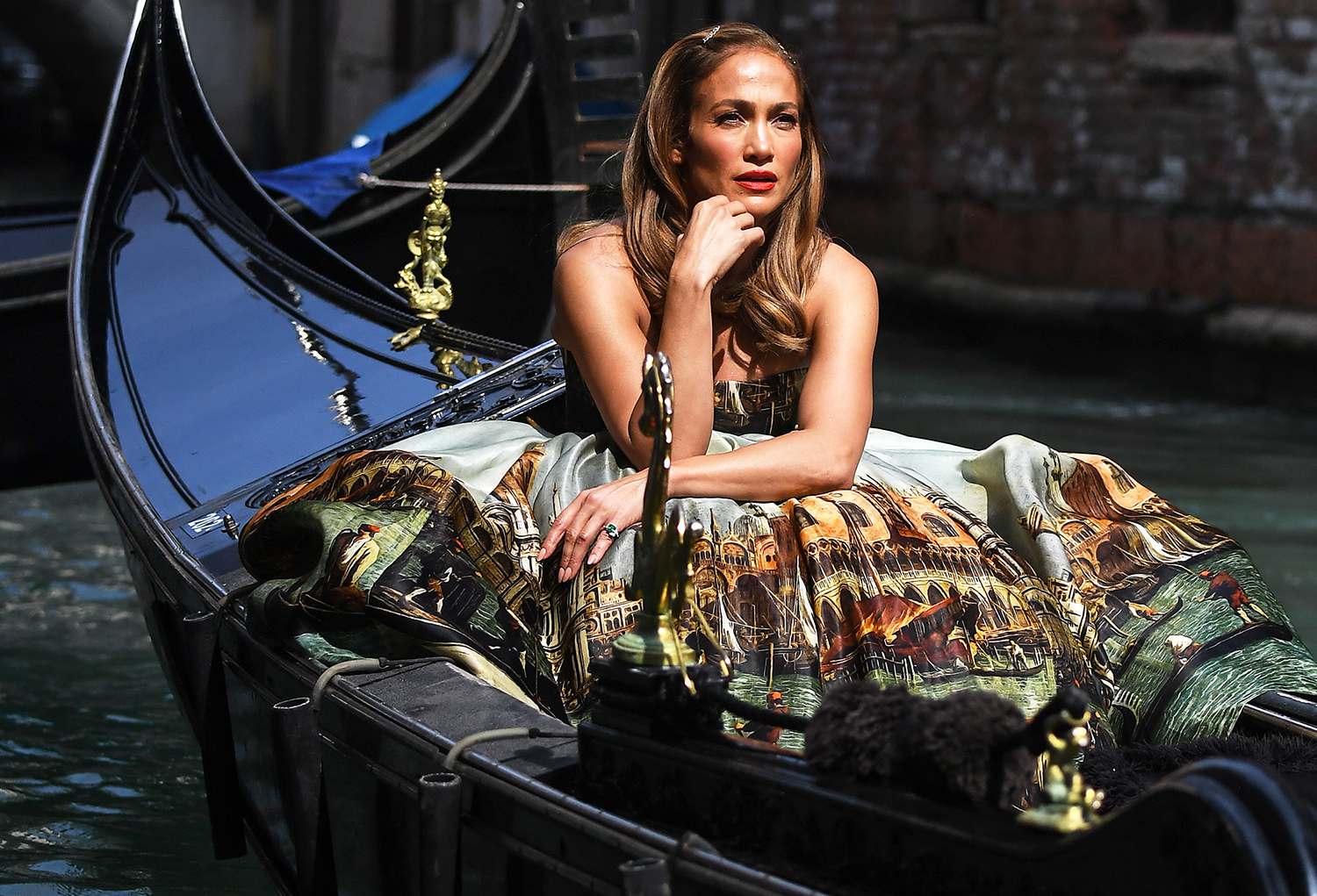 09/11/2021 Jennifer Lopez is seen on a gondola in Venice, Italy. The 52 year old took to the water for a stunning photoshoot wearing a Dolce & Gabbana strapless tulle ballgown.