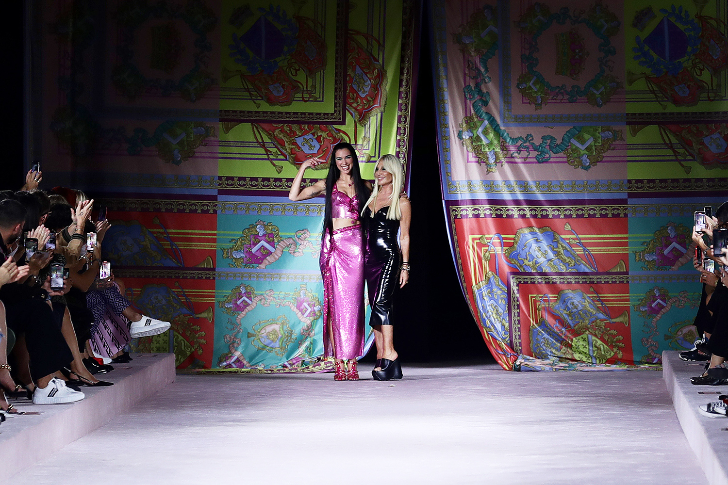 Dua Lipa and fashion designer Donatella Versace acknowledge the applause of the audience at the runwayat the Versace fashion show during the Milan Fashion Week - Spring / Summer 2022 on September 24, 2021 in Milan, Italy.