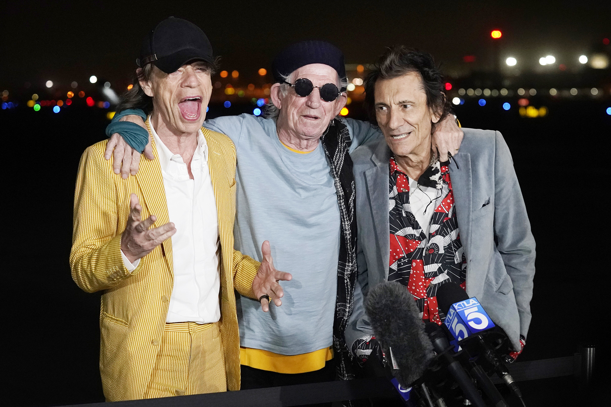 """Mick Jagger, left, Keith Richards, center, and Ron Wood of The Rolling Stones take questions from reporters after their plane landed at Hollywood Burbank Airport in Burbank, Calif., ahead of their shows this week at SoFi Stadium in Inglewood, Calif., for their """"NO FILTER"""" tour Rolling Stones Arrive in Los Angeles, Burbank, United States - 11 Oct 2021"""