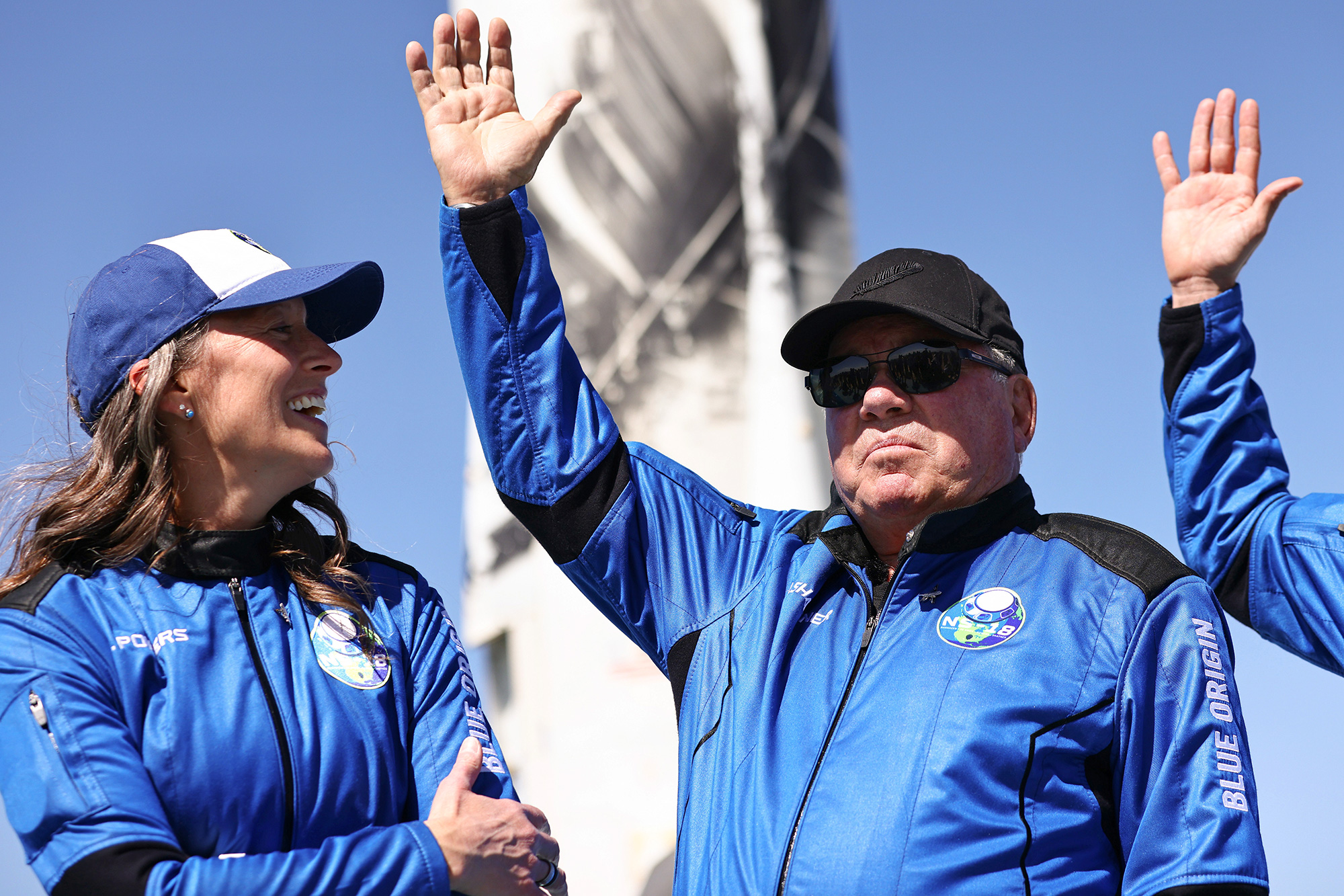 Blue Origins vice president of mission and flight operations Audrey Powers (L) looks on as Star Trek actor William Shatner waves during a media availability on the landing pad of Blue Origin's New Shepard after they flew into space on October 13, 2021 near Van Horn, Texas.