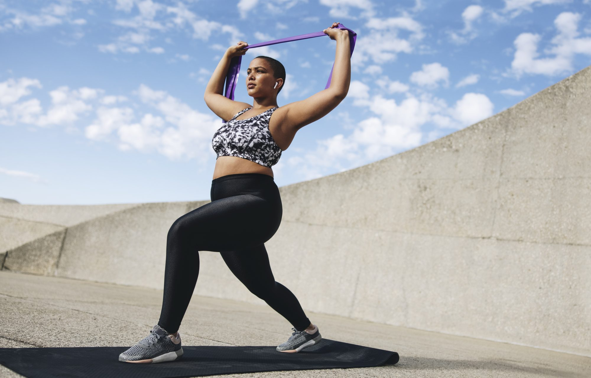 Best Black Leggings, According to Customer Reviews , Plus size woman exercising with resistance band
