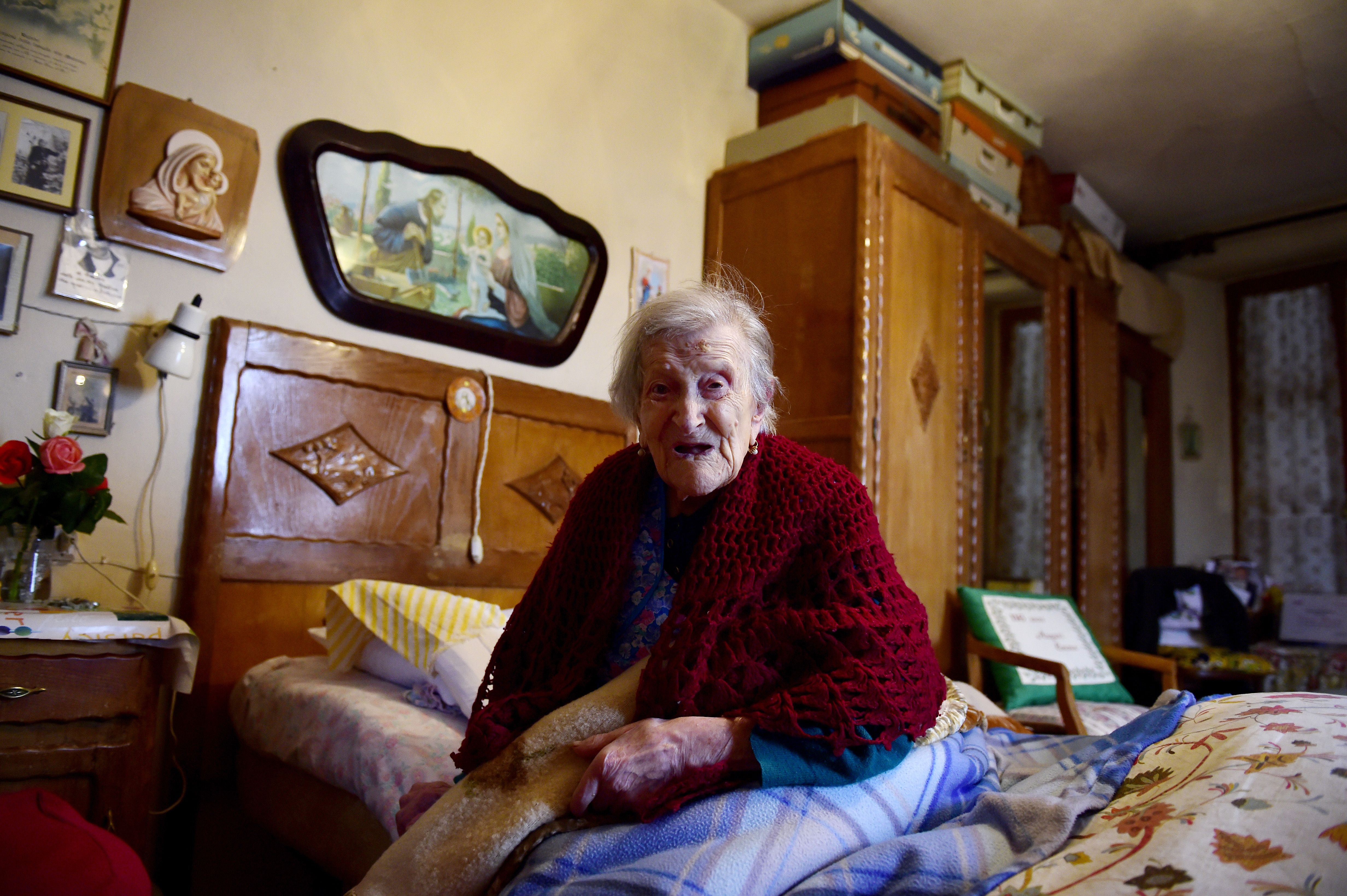 """Emma Morano, 116, holds a pillow reading """"116 years old, Happy Birthday Emma"""" as she poses for AFP photographer in Verbania, North Italy, on May 14, 2016. Emma Morano is the oldest living person in the world, and the only one left who has touched three centuries. Susannah Mushatt Jones, a New York woman several months her senior, died on May 12 evening, making Morano the world's oldest known person at 116. / AFP / OLIVIER MORIN (Photo credit should read OLIVIER MORIN/AFP/Getty Images)"""