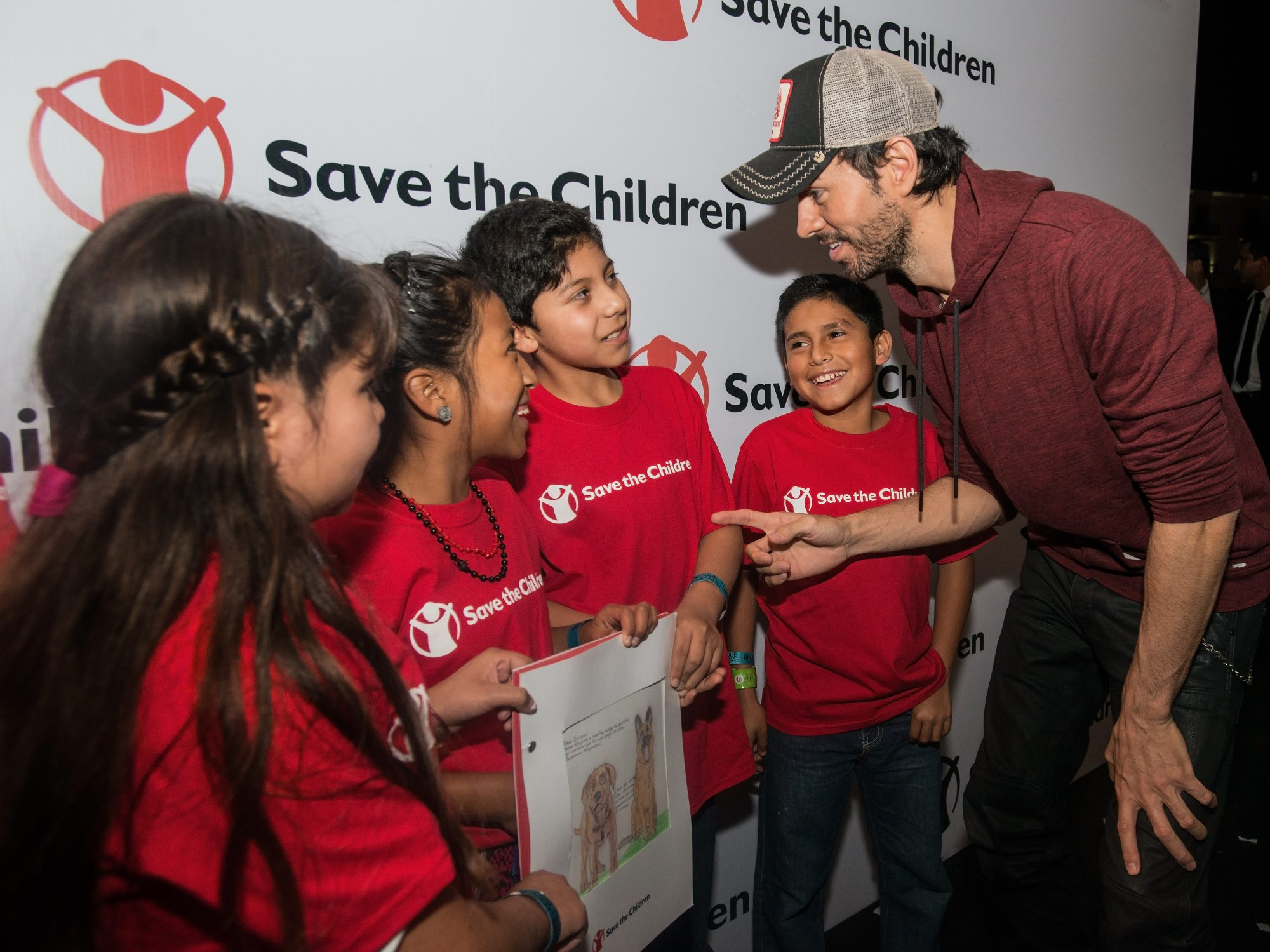 Photos are Embargoed until Tuesday December 13th, 2016. EXCLUSIVE PHOTO FOR PEOPLE: International pop star Enrique Iglesias talks with, from left, Henely, Juana, Gerson and Julio, before his Dec. 9, 2016, concert in Guatemala City, Guatemala. The kids, who all participate in Save the Children's Literacy Boost program in Guatemala, created a handmade book as a thank you gift for Iglesias, who, through a partnership with Microsoft, has donated $200,000 in software to Save the Children to strengthen its literacy programming for elementary school-age children in El Salvador, Guatemala and Peru.