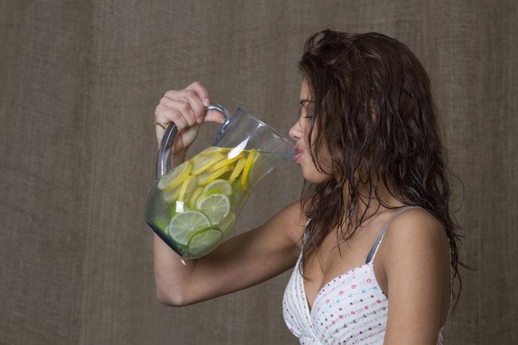 Mujer tomando agua con limón