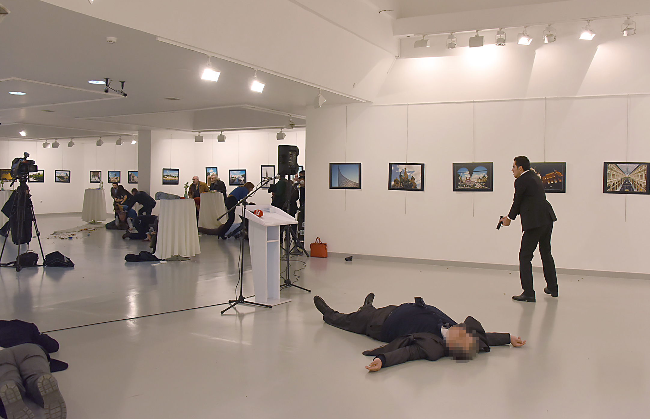 """EDITORS NOTE: Graphic content / This picture taken on December 19, 2016 shows Andrey Karlov (2ndR), the Russian ambassador to Ankara, lying on the floor after being shot by a gunman (R) during an attack during a public event in Ankara. A gunman crying """"Aleppo"""" and """"revenge"""" shot Karlov while he was visiting an art exhibition in Ankara on December 19, witnesses and media reports said. The Turkish state-run Anadolu news agency said the gunman had been """"neutralised"""" in a police operation, without giving further details. / AFP / STRINGER (Photo credit should read STRINGER/AFP/Getty Images)"""