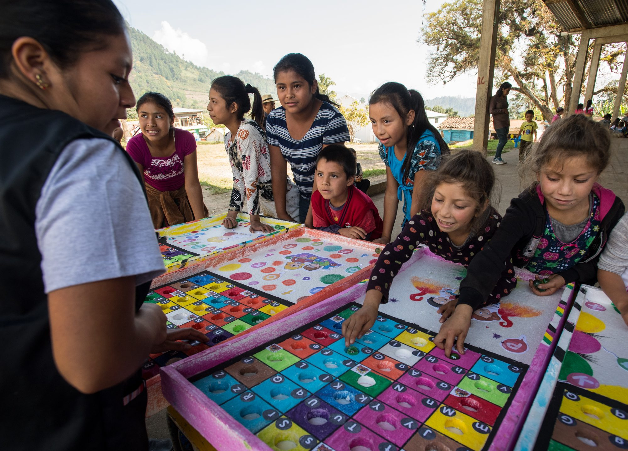 """In the """"Marble Letter"""" game at Save the Children's reading festival, children are challenged to recite a word that begins with the letter their marble lands in. The materials for the game are made locally by the volunteers in Guatemala's remote mountainous region of Quiche."""