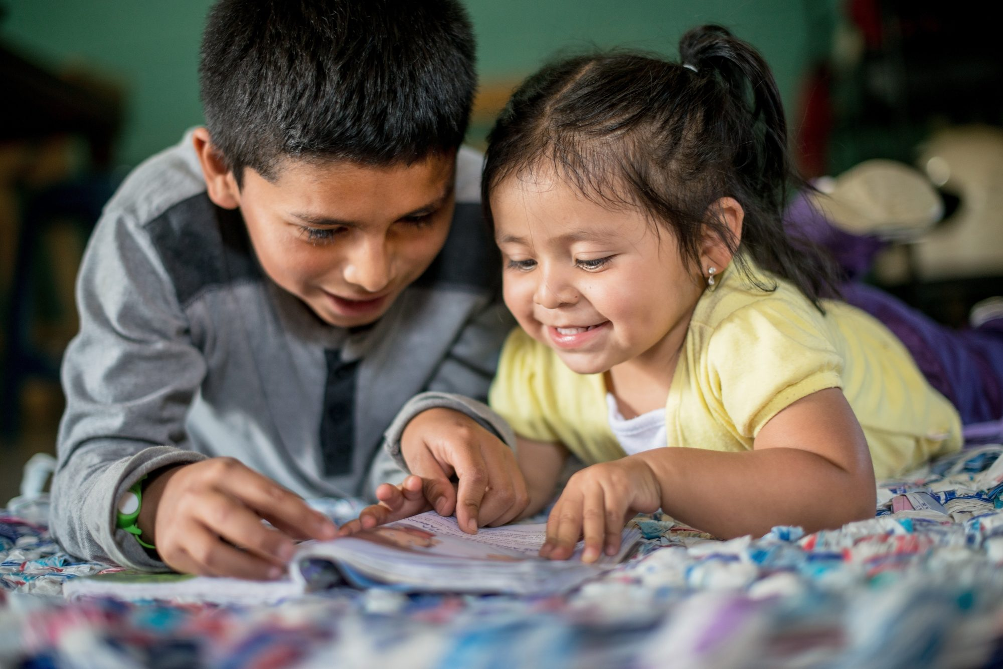 Julio, 11, reads with his 18-month-old sister, Ariana. Just completing the fifth grade, Julio also participates in Save the Children's Literacy Boost program at his school in Guatemala's remote mountainous region of Quiche.