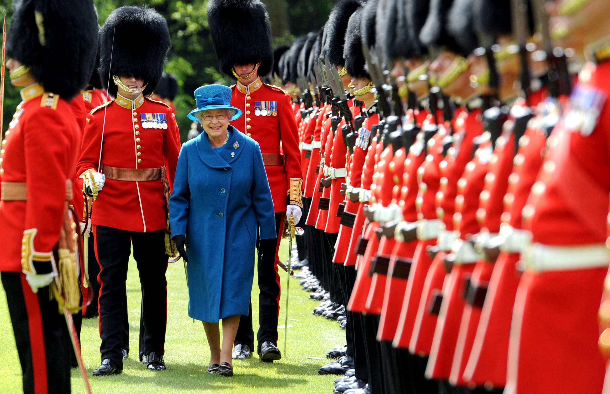 LONDON - MAY 11: Queen Elizabeth II inspects the Grenadier Guards before presenting their new colours in the garden of Buckingham Palace on May 11, 2010 in London, England. The Queen paid tribute to the families of Grenadier Guardsmen killed while fighting in Afghanistan and comrades wounded in action as she presented the regiment with new colours today. (Photo by Anthony Devlin/WPA Pool/Getty Images)