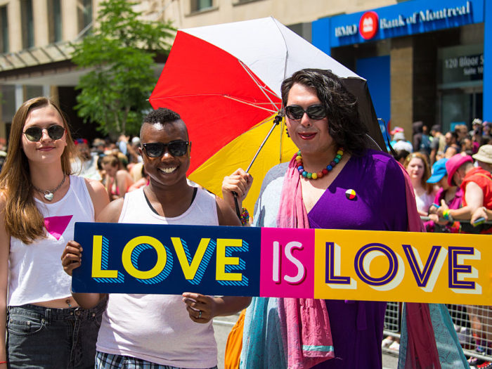 Love is Love sign held by multicultural attendees in the
