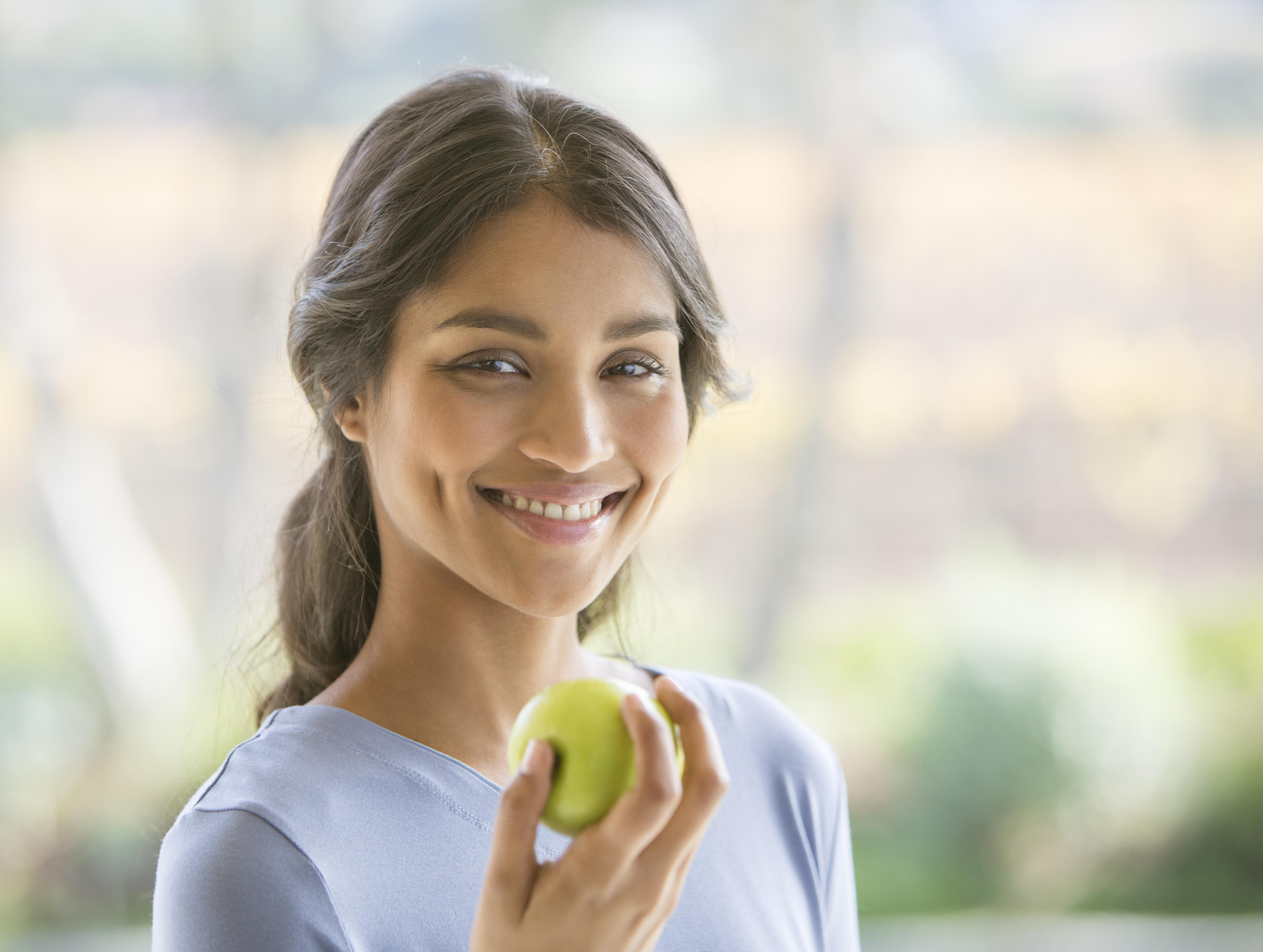 Chica saludable comiendo manzana.