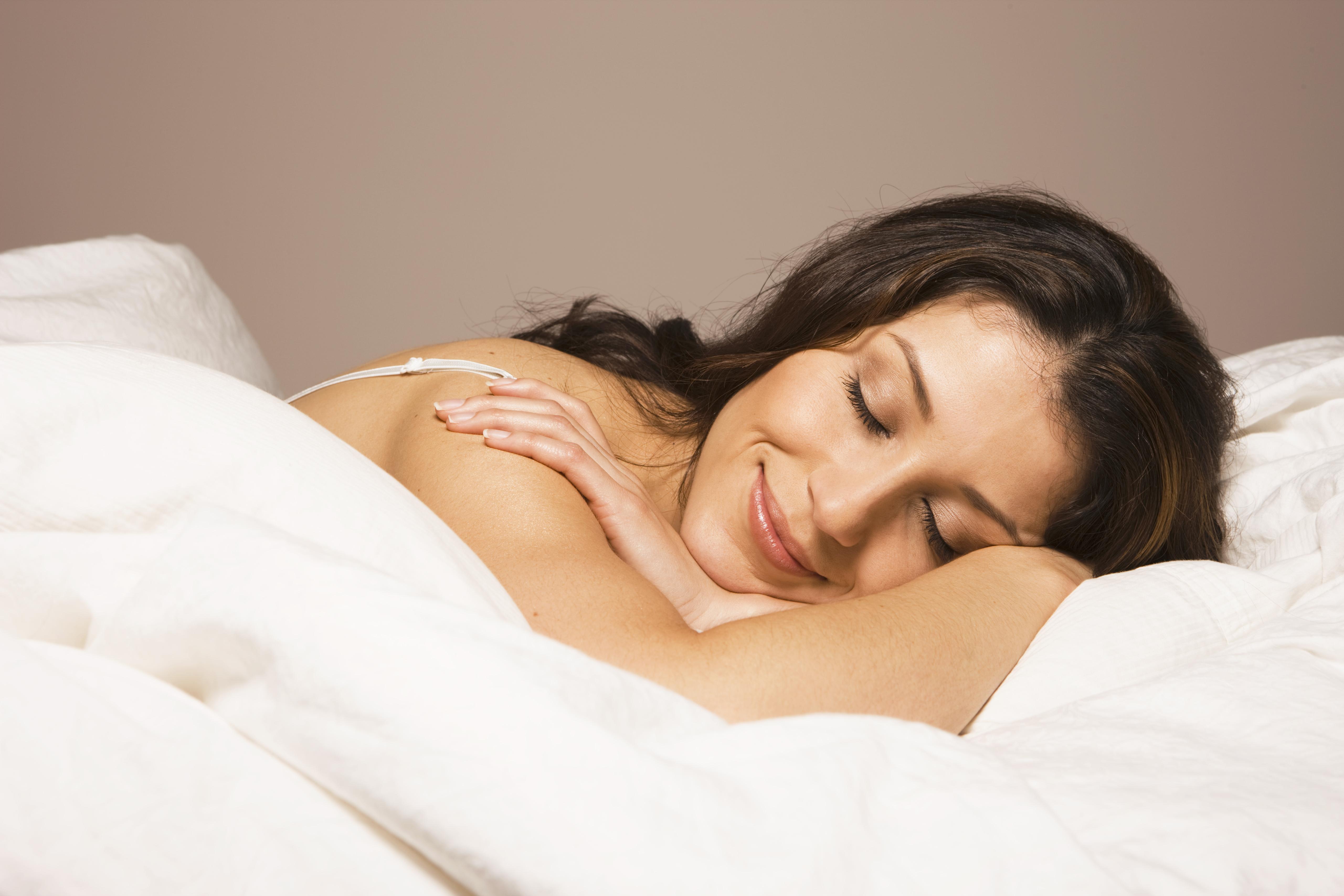 hispanic woman laying in bed smiling