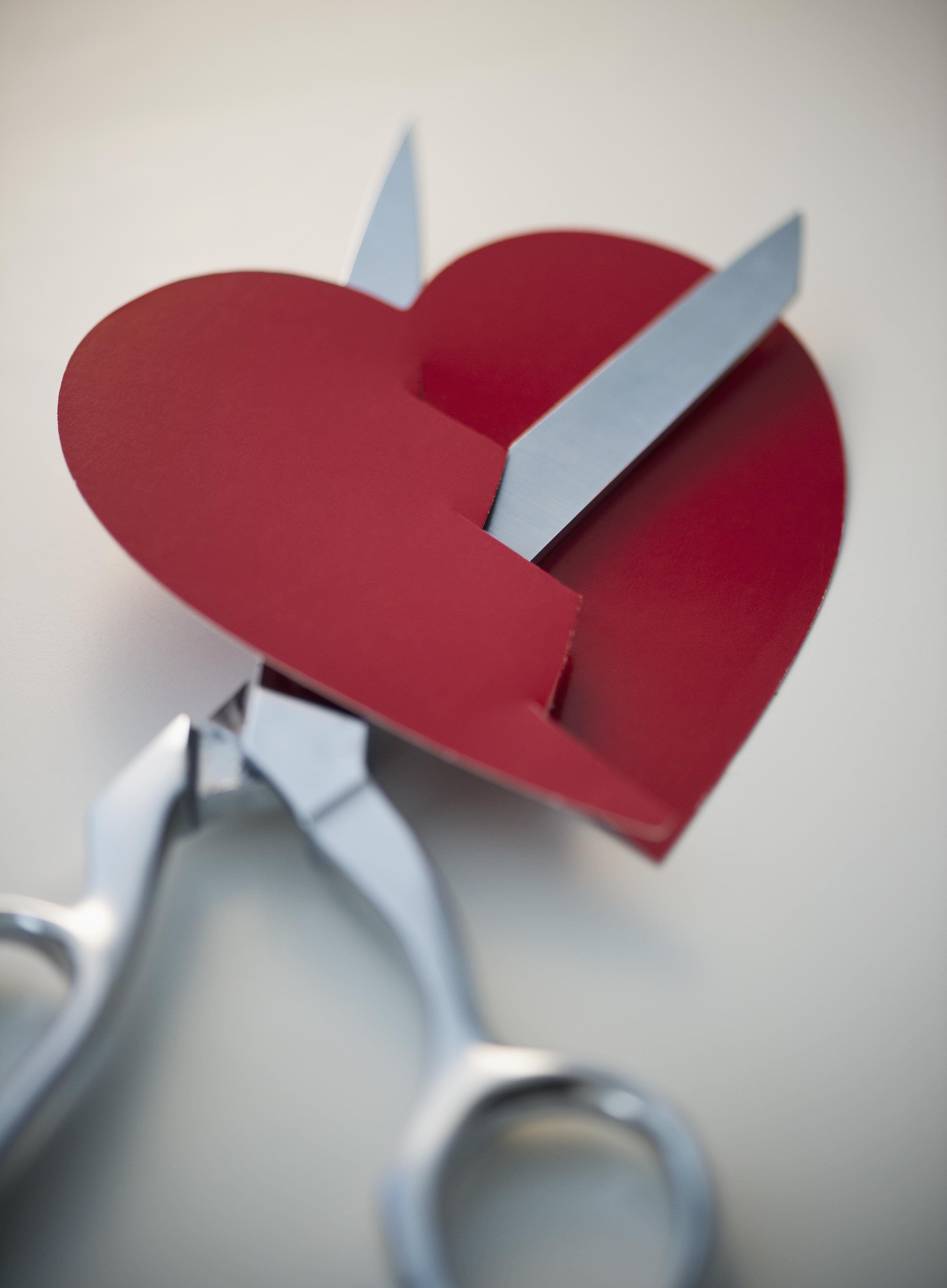 Scissors cutting paper heart
