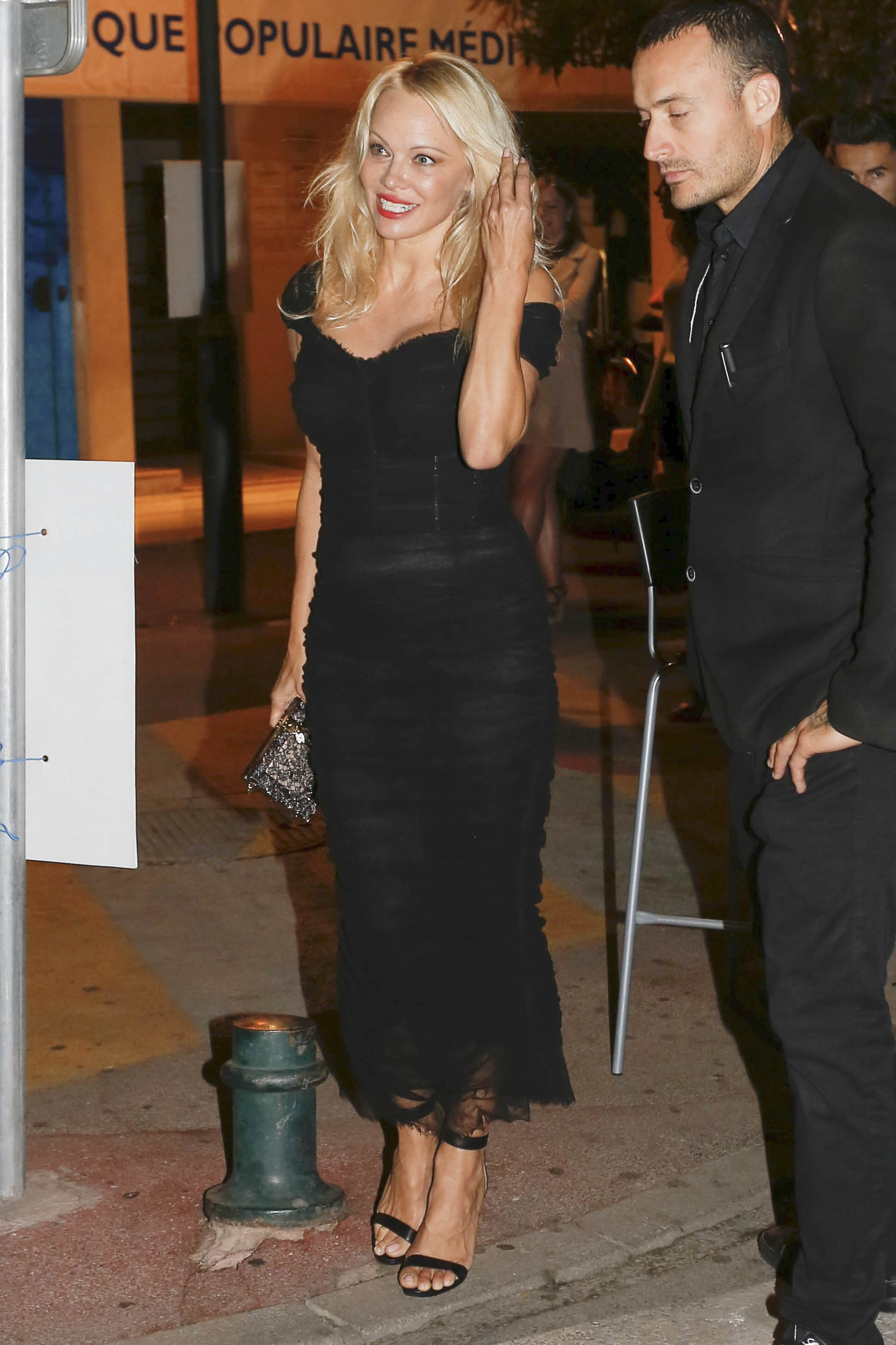 Pamela Anderson Flashes her Famous Curves while Leaving Vip Room in St Tropez with Male Friend
