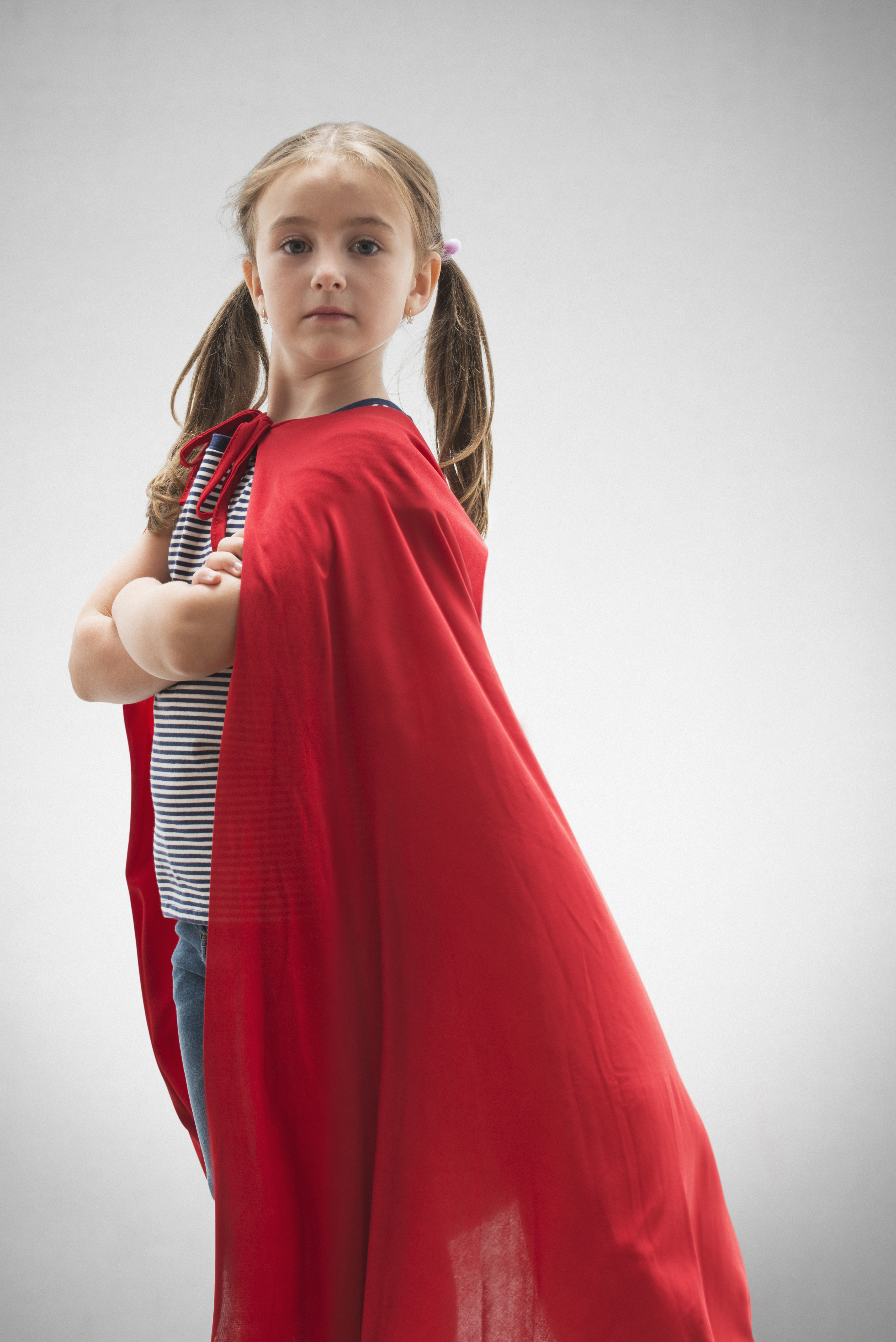 Caucasian girl wearing superhero cape