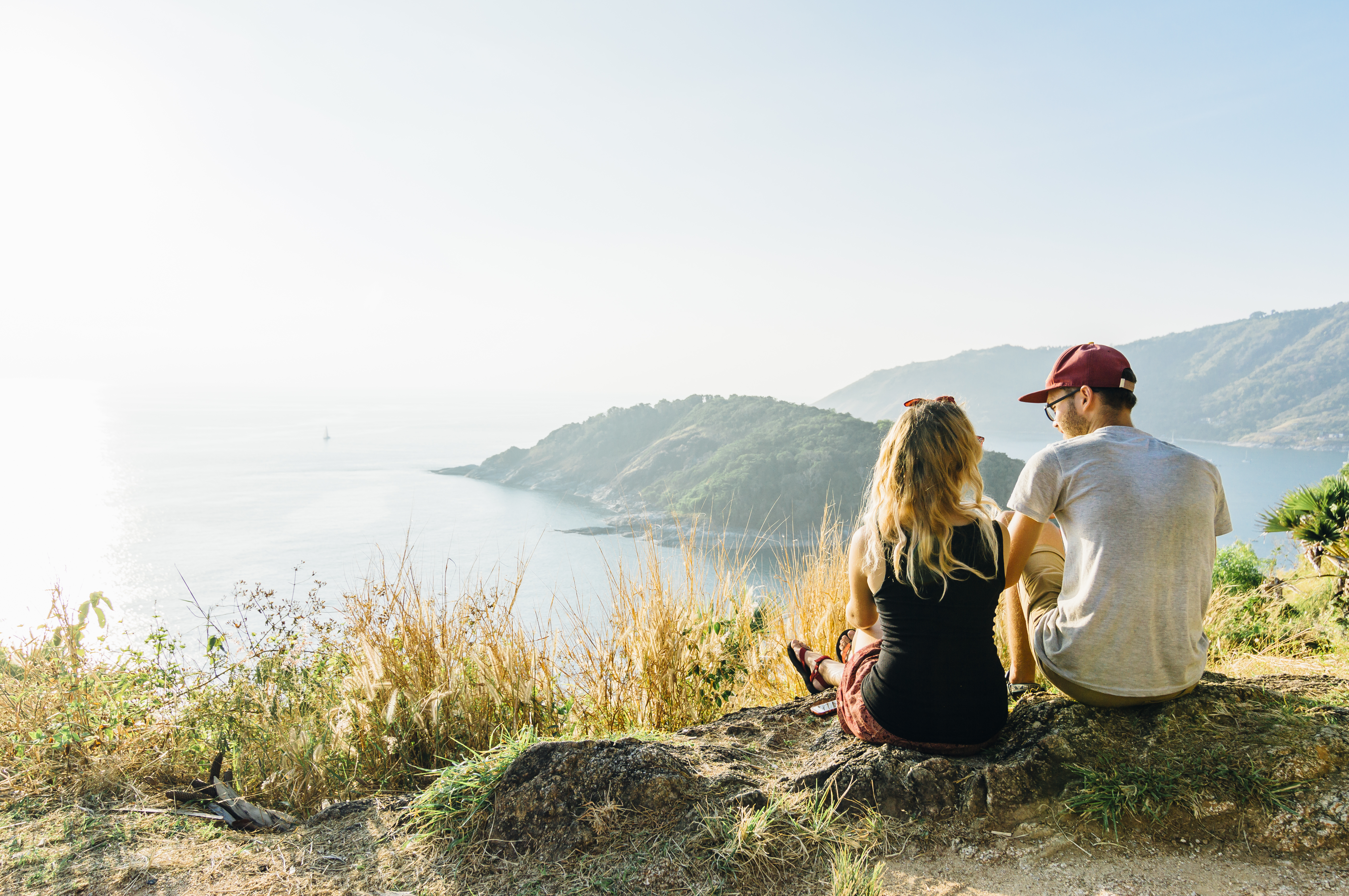 Young couple relax, on hillside above sea
