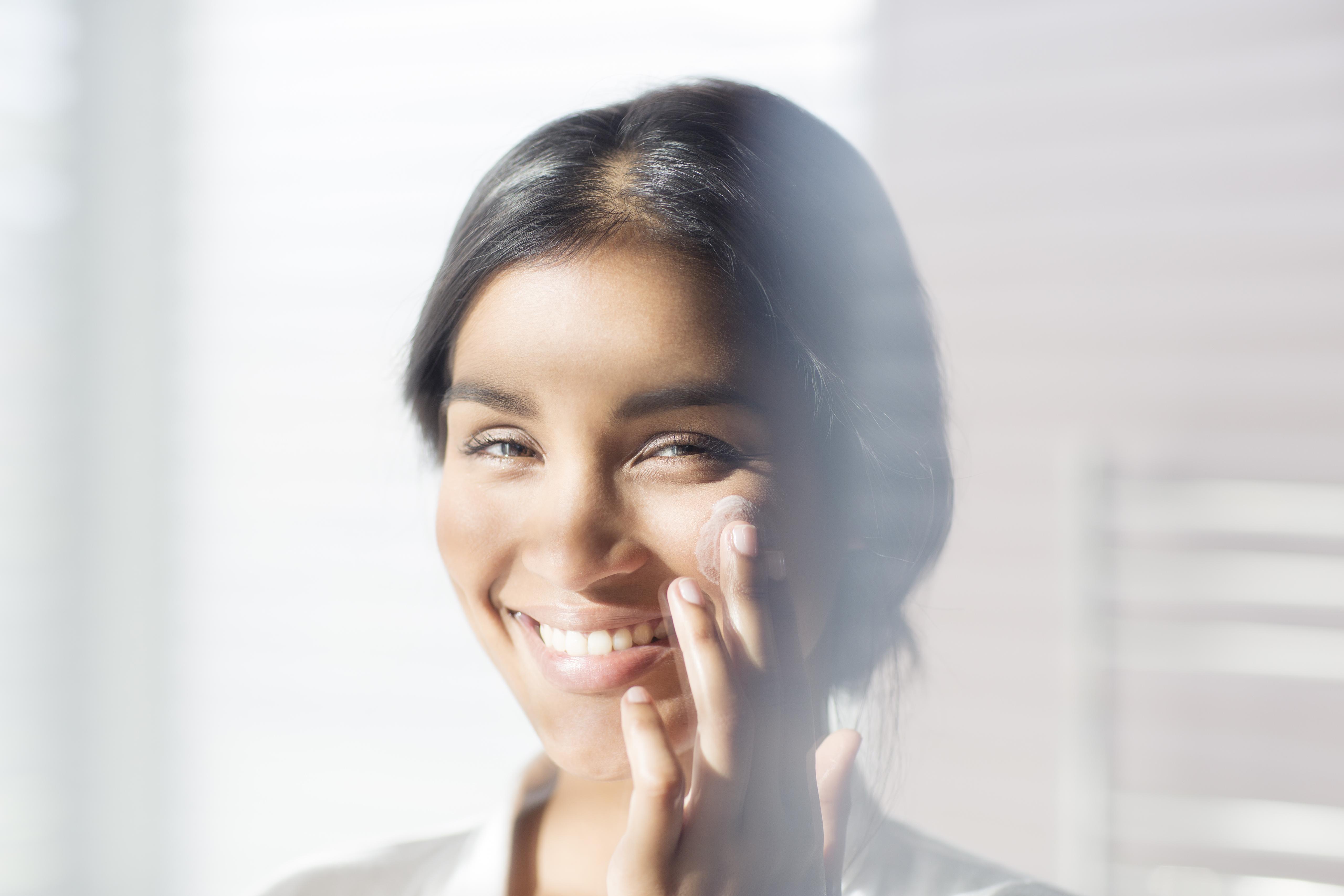 Close up portrait smiling woman applying moisturizer to cheek