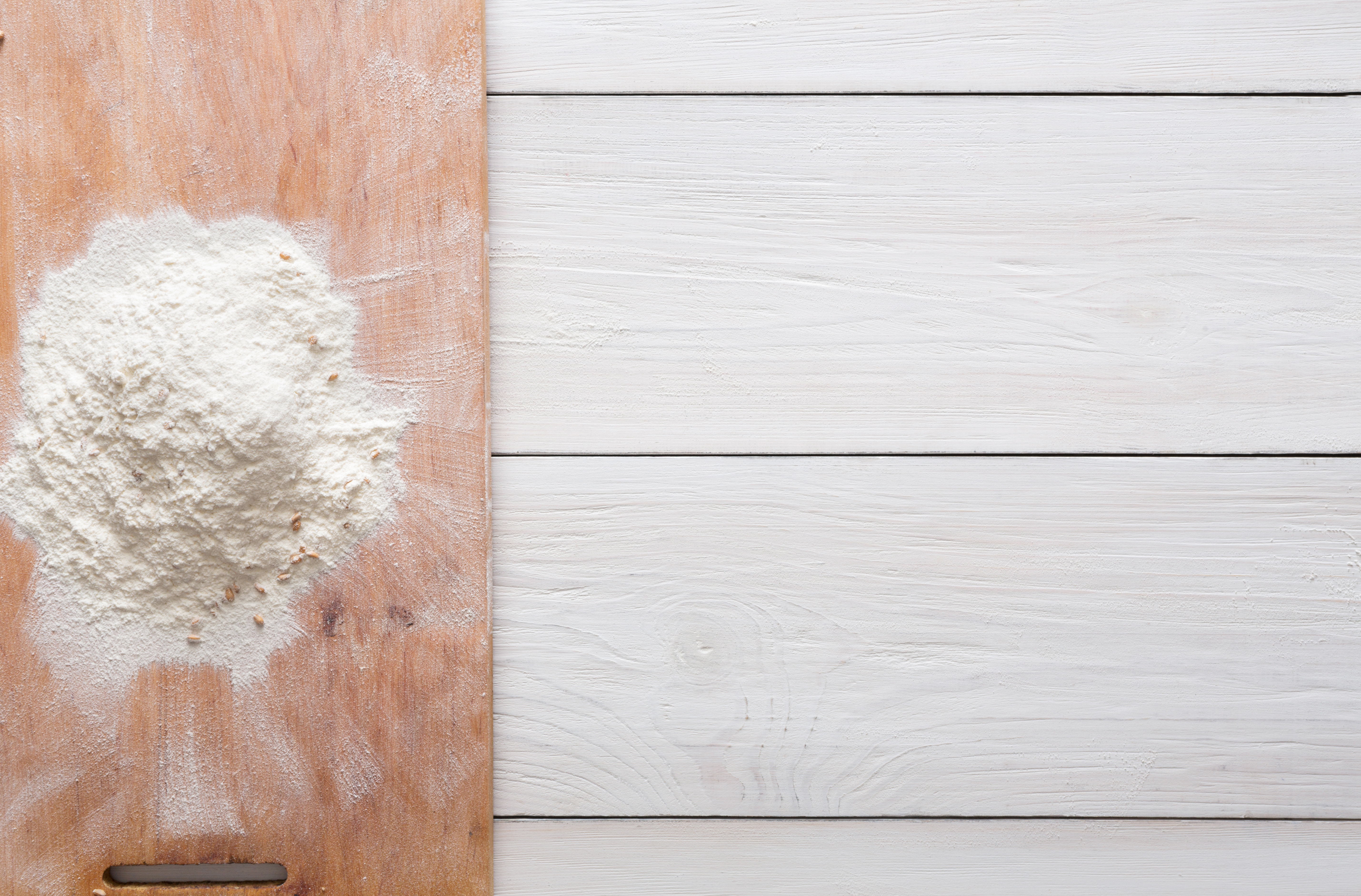 Baking concept on white wood background, sprinkled flour with copy space