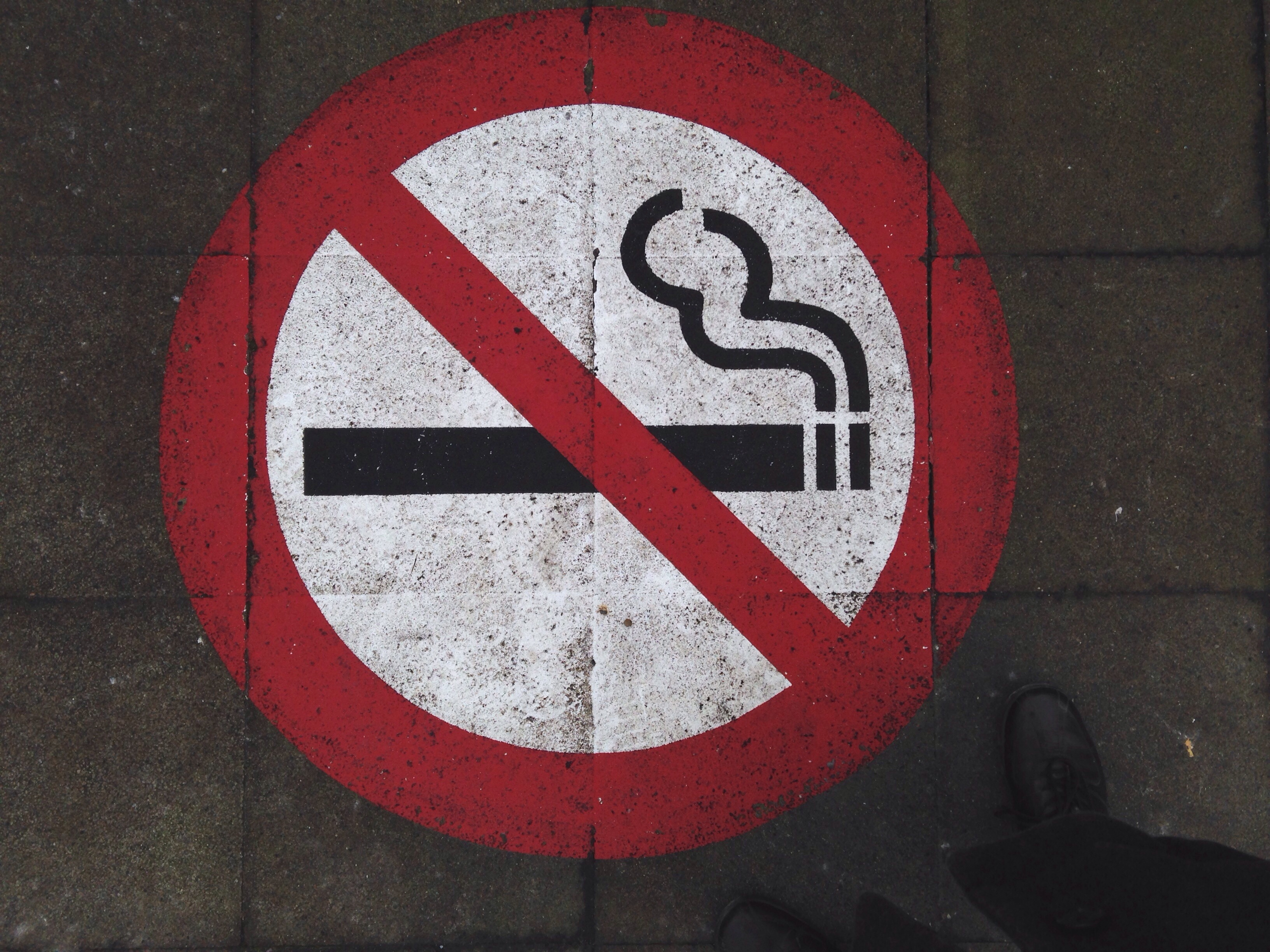 Low Section Of Man Standing By No Smoking Sign On Footpath