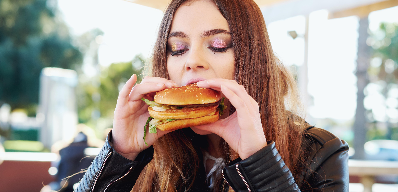 Close-Up Of Teenager Eating Burger While Sitting At Restaurant