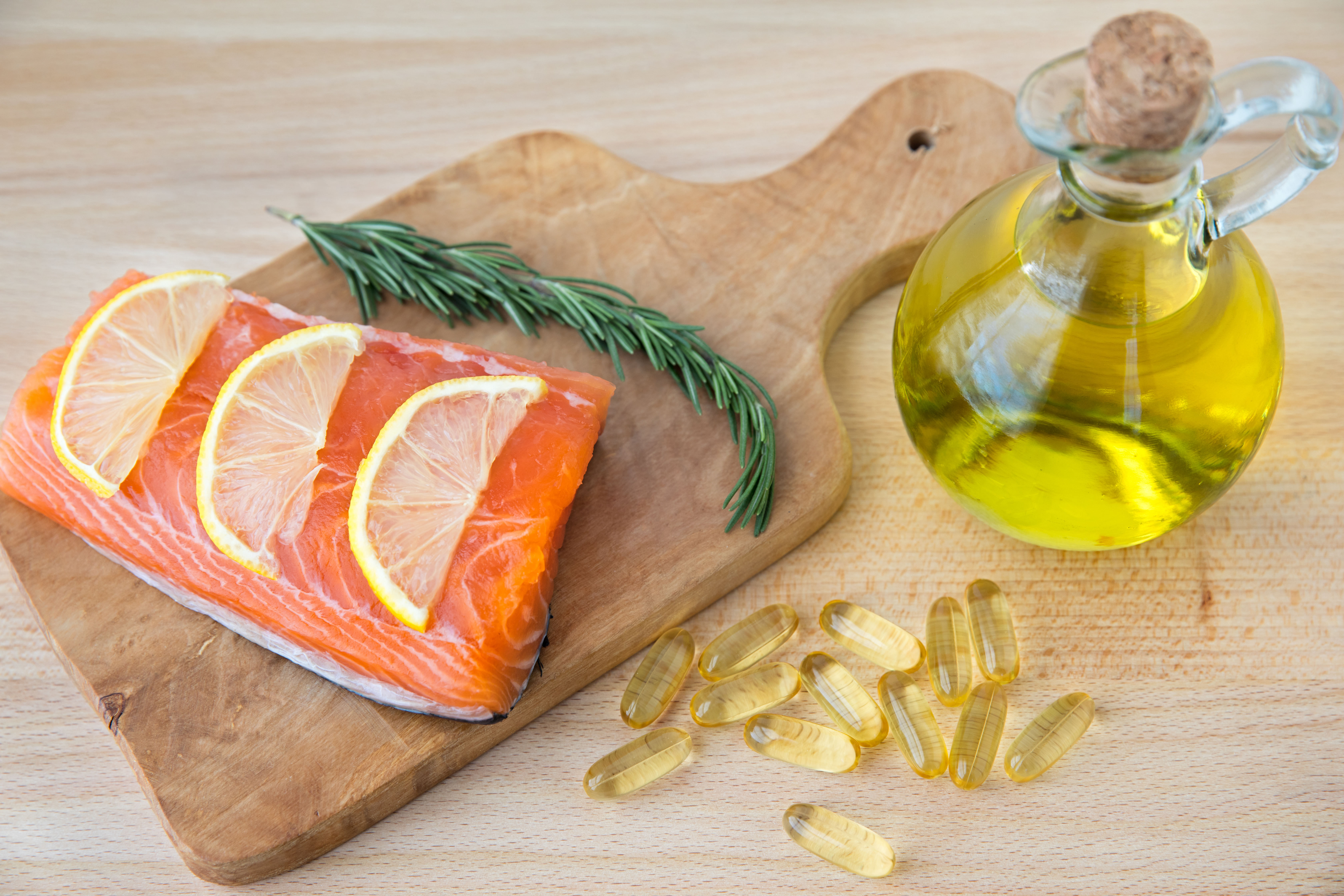 Fish oil capsules, cod liver, and salmon fillet on wooden surface