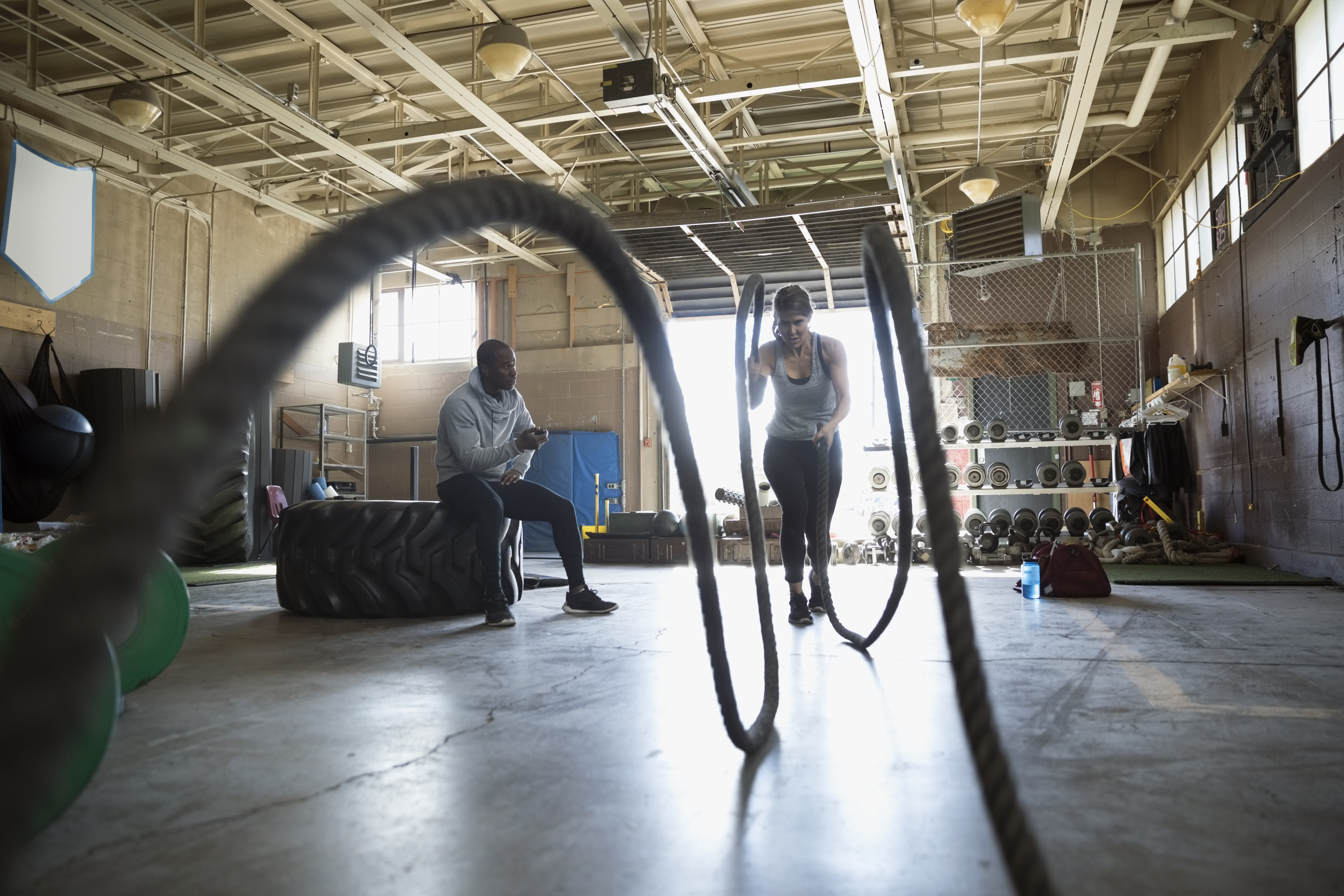 Male personal trainer watching female client doing gym battling ropes exercise in gym
