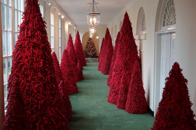 More than 40 red topiary trees line the East colonnade as part of the holiday decorations at the White House.