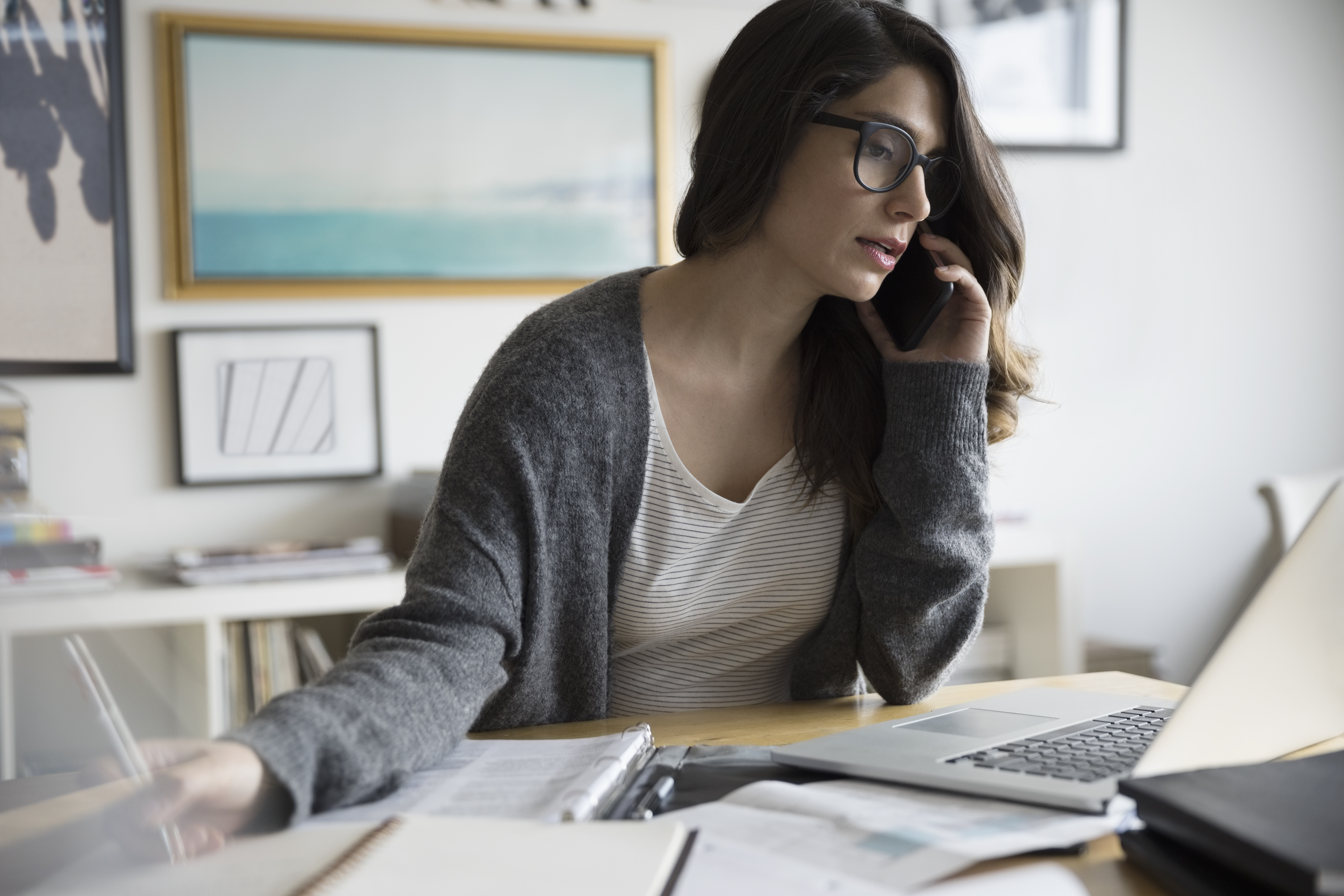 Businesswoman talking on smart phone and working in office