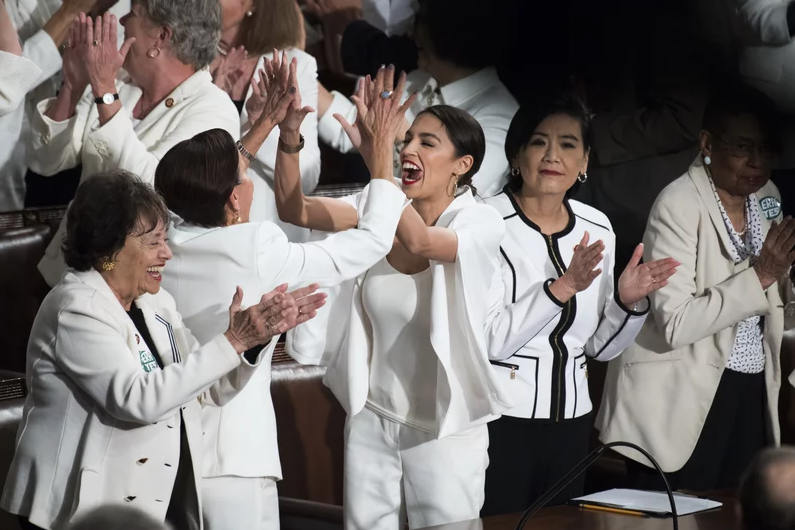 Alexandria Ocasio-Cortez, D-N.Y., right, high fives Nydia Velazquez, D-N.Y., as Democratic members celebrate in the House Chamber as President Donald Trump recognized their achievement of electing a record number of women to Congress, during the State of the Union address on Tuesday, February 5, 2019. (Photo By Tom Williams/CQ Roll Call)